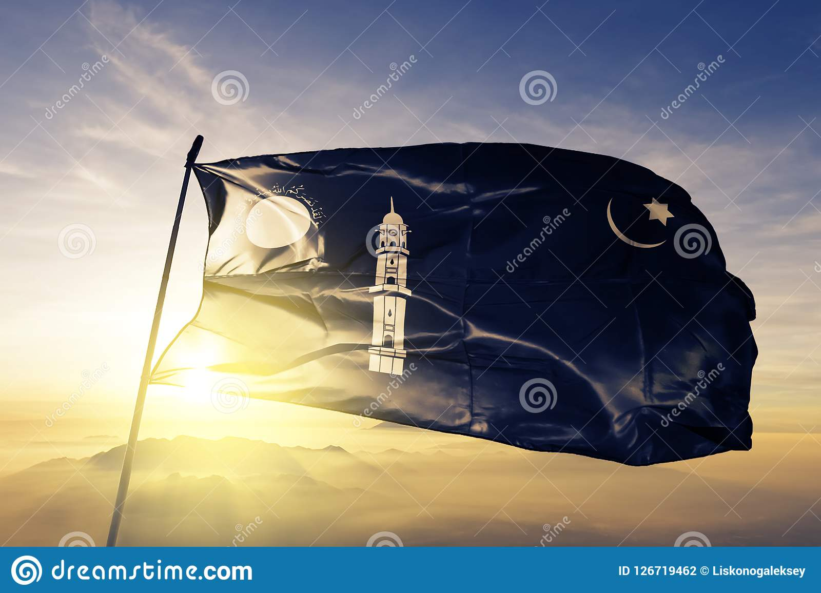 Ahmadiyya Muslim Community flag textile cloth fabric waving on the top sunrise mist fog