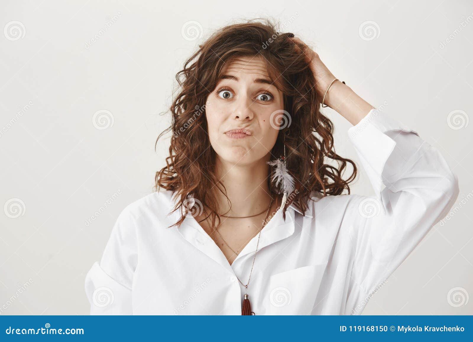 Ahnungsloses und verwirrtes reizend kaukasisches Frauenverkratzen Haupt und Die Stirn runzeln mit dem verwirrten Ausdruck, stehen