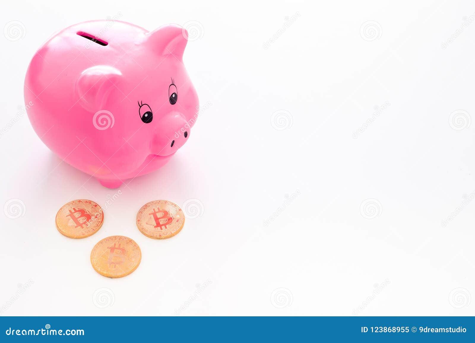 Ahorros Moneybox en la forma del cerdo cerca de monedas en el espacio blanco de la copia del fondo