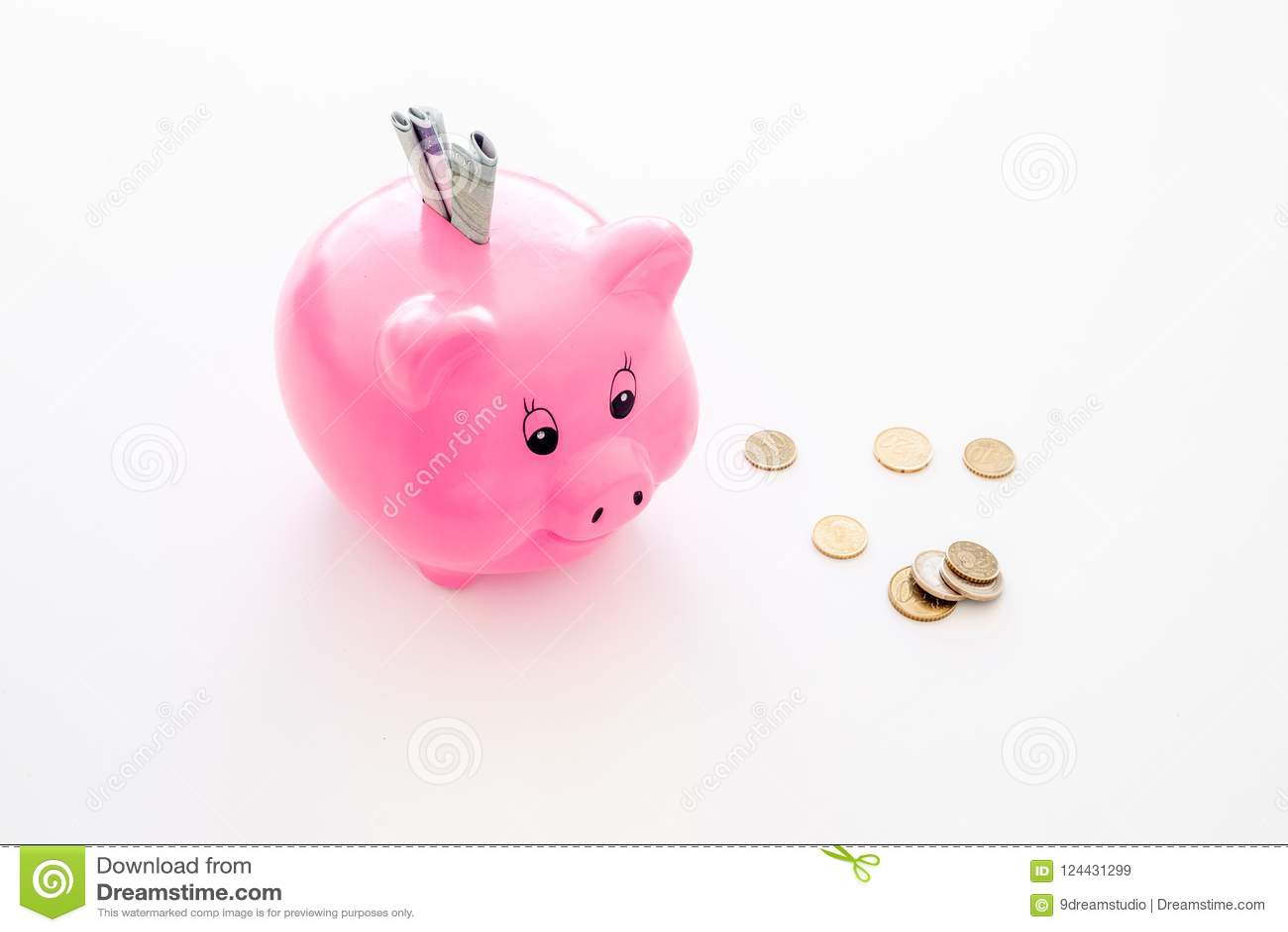 Ahorros Moneybox en la forma del cerdo con los billetes de banco que caen en ella cerca de monedas en el espacio blanco de la cop