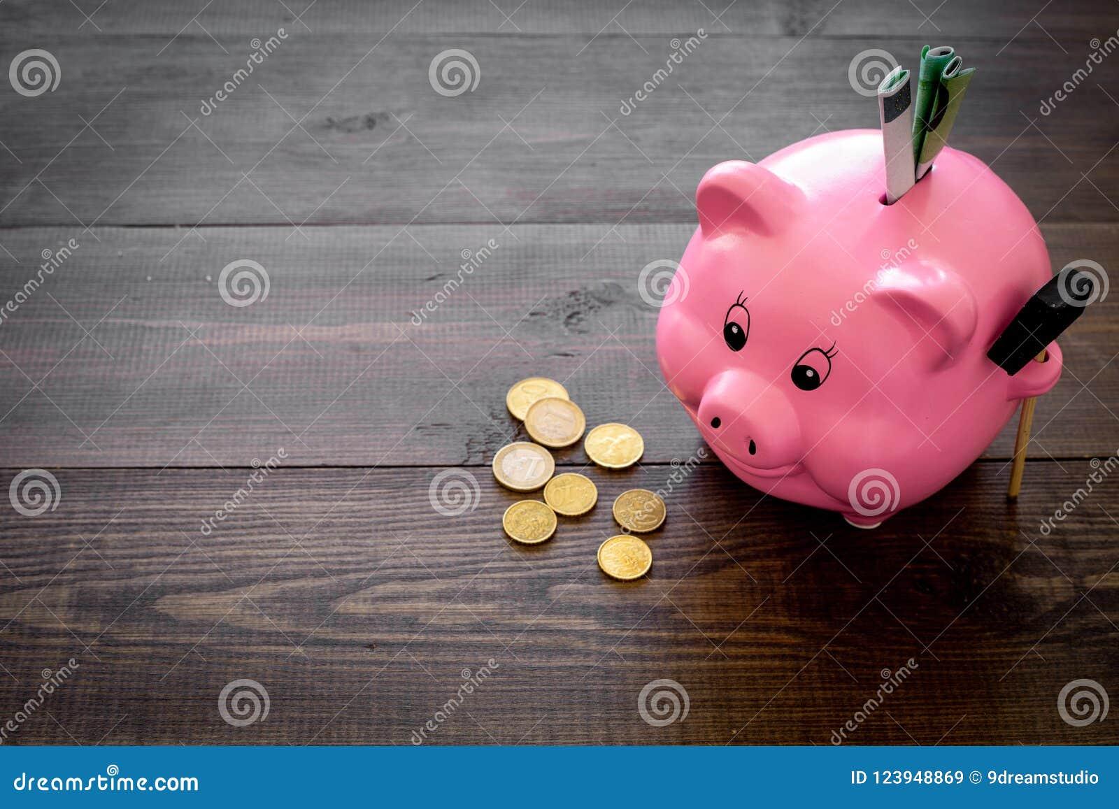 Ahorros Moneybox en la forma del cerdo con los billetes de banco que caen en ella cerca de monedas en el espacio de madera oscuro
