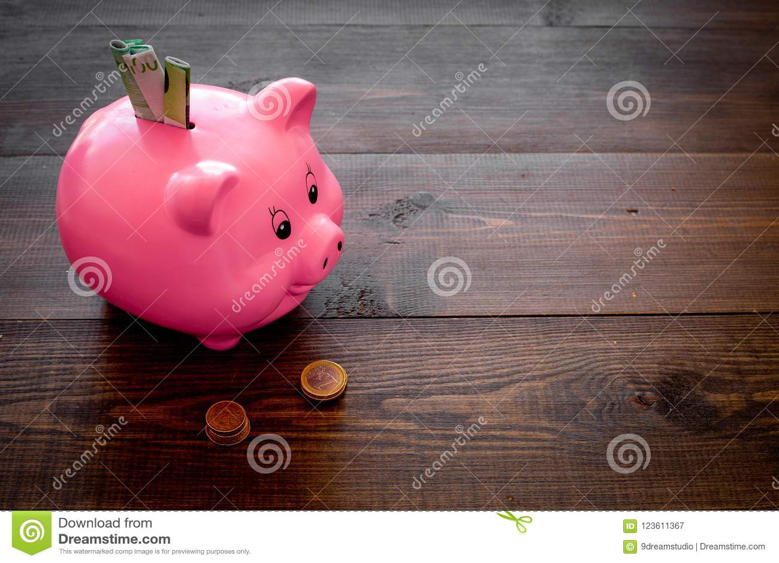 Ahorros Moneybox en la forma del cerdo con los billetes de banco que caen en ella cerca de monedas en espacio de madera oscuro de