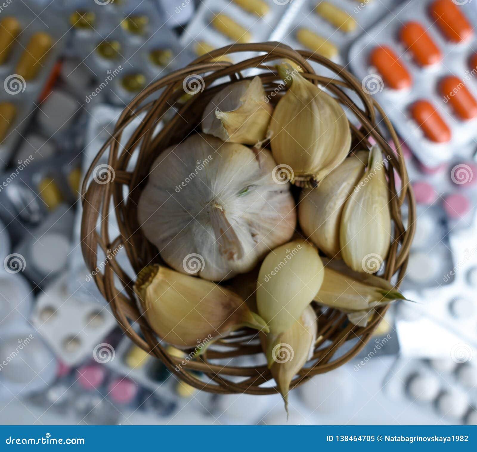 Ail et pilules sur le fond blanc