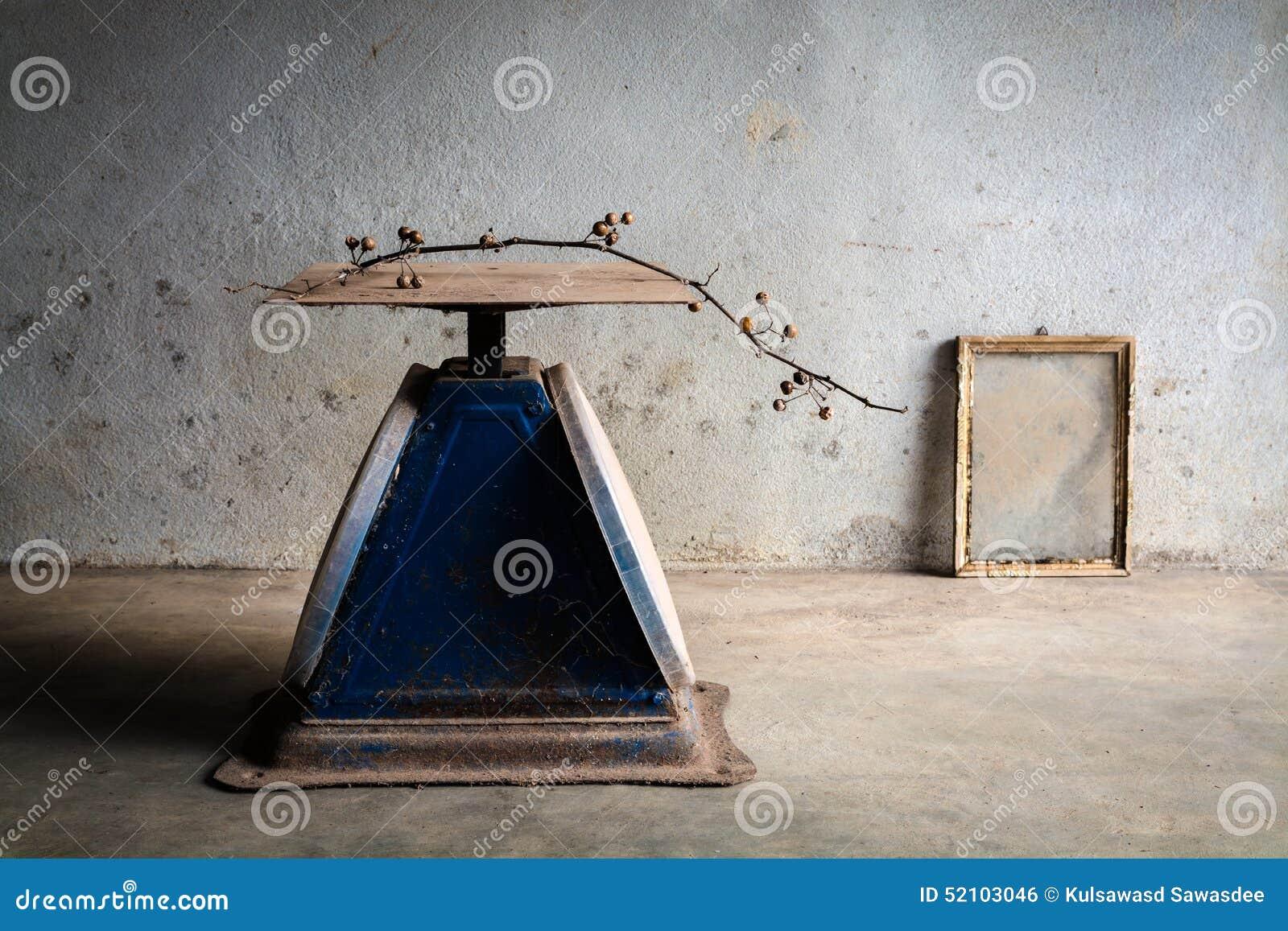 Ainda vida com as escalas velhas do azul e quadro velho da foto na parede do cimento