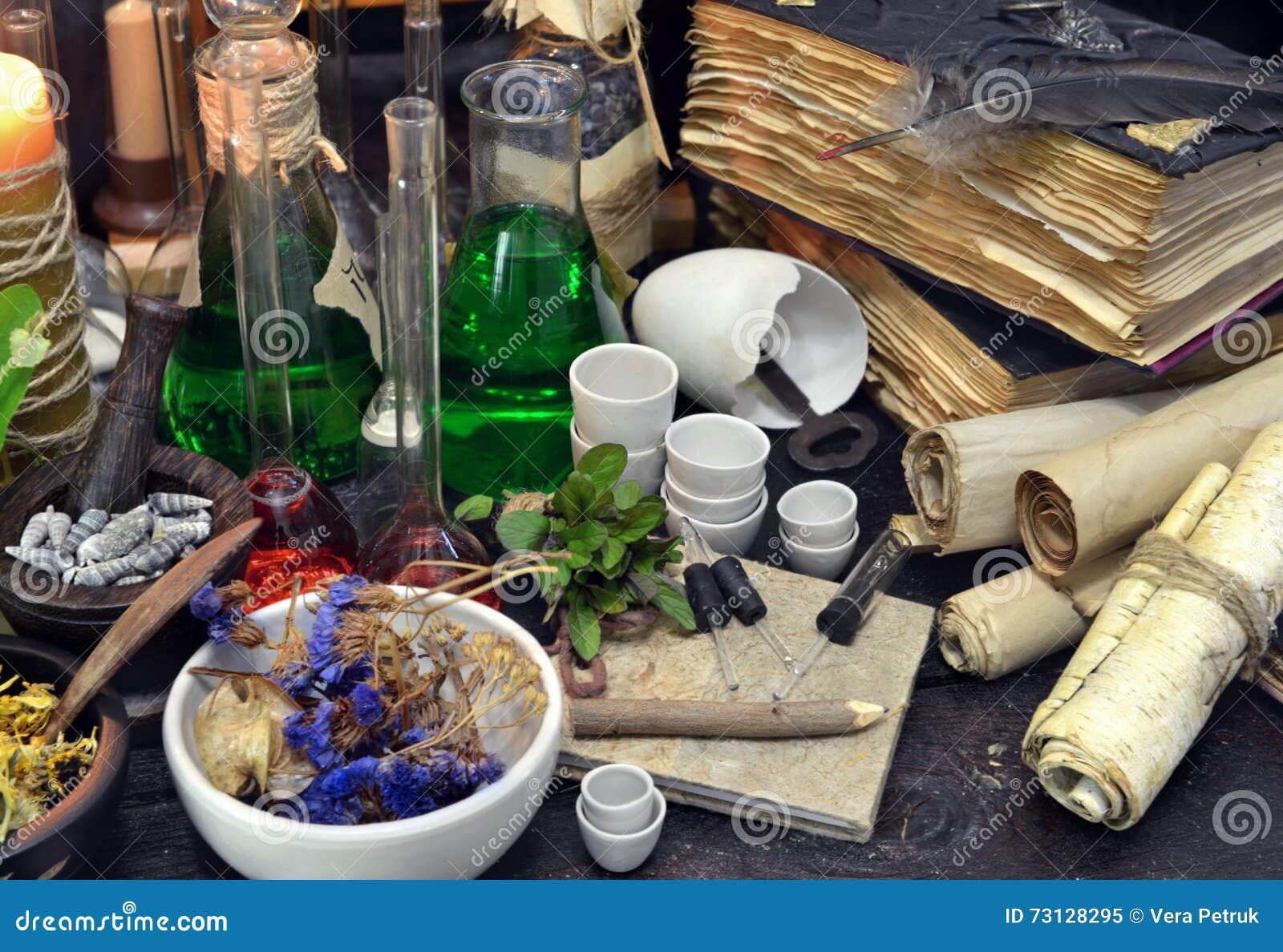 Ainda vida com garrafas, componentes mágicos, rolos e livros