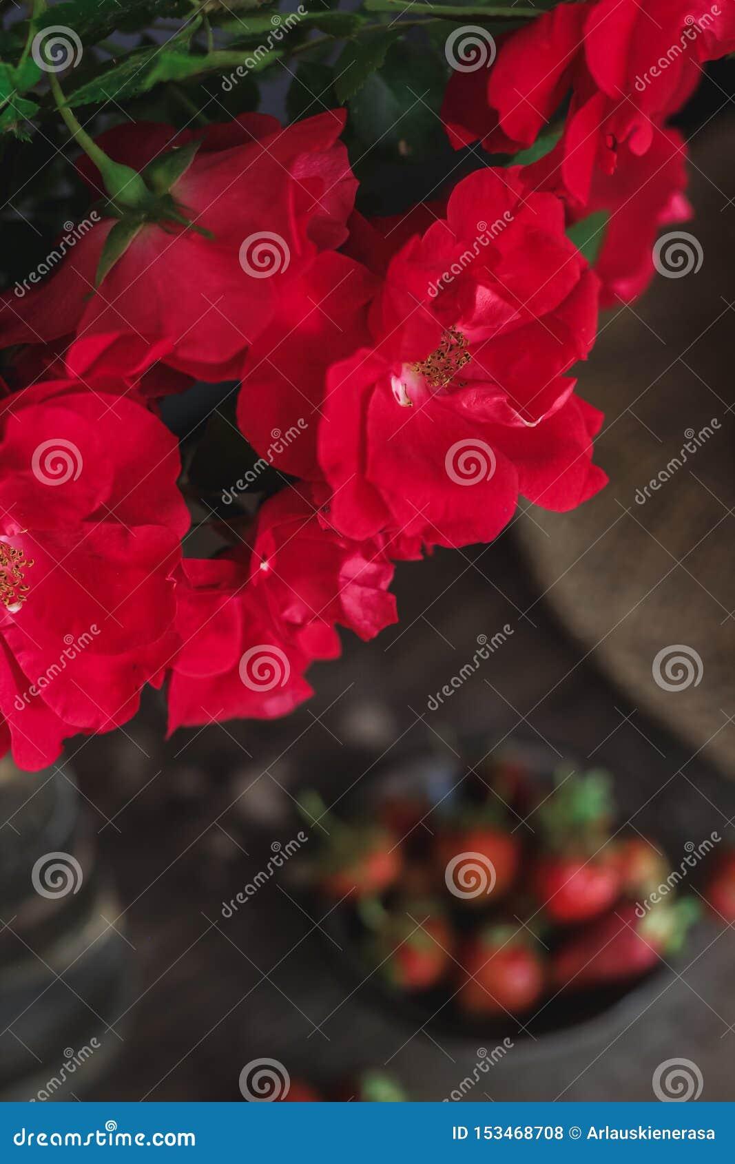 Ainda vida com rosas vermelhas, morangos e um chapéu