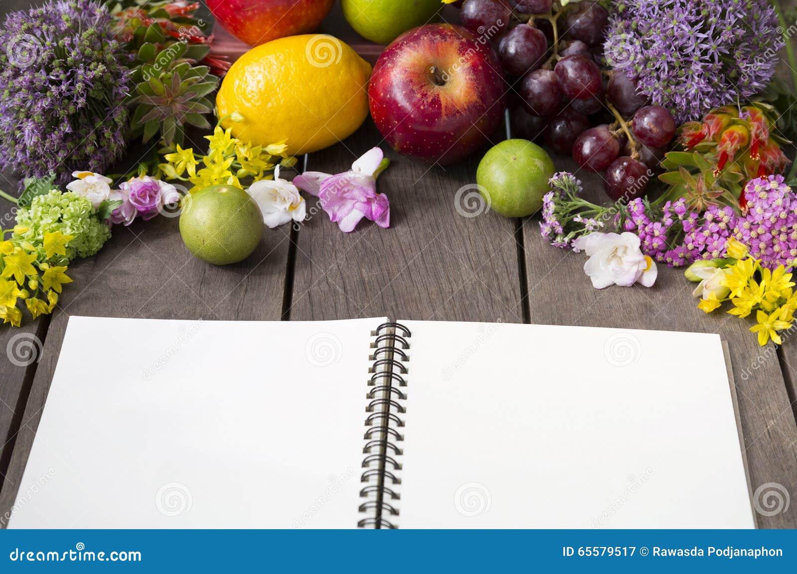 Ainda vida de arranjar flores e fruto no fundo de madeira