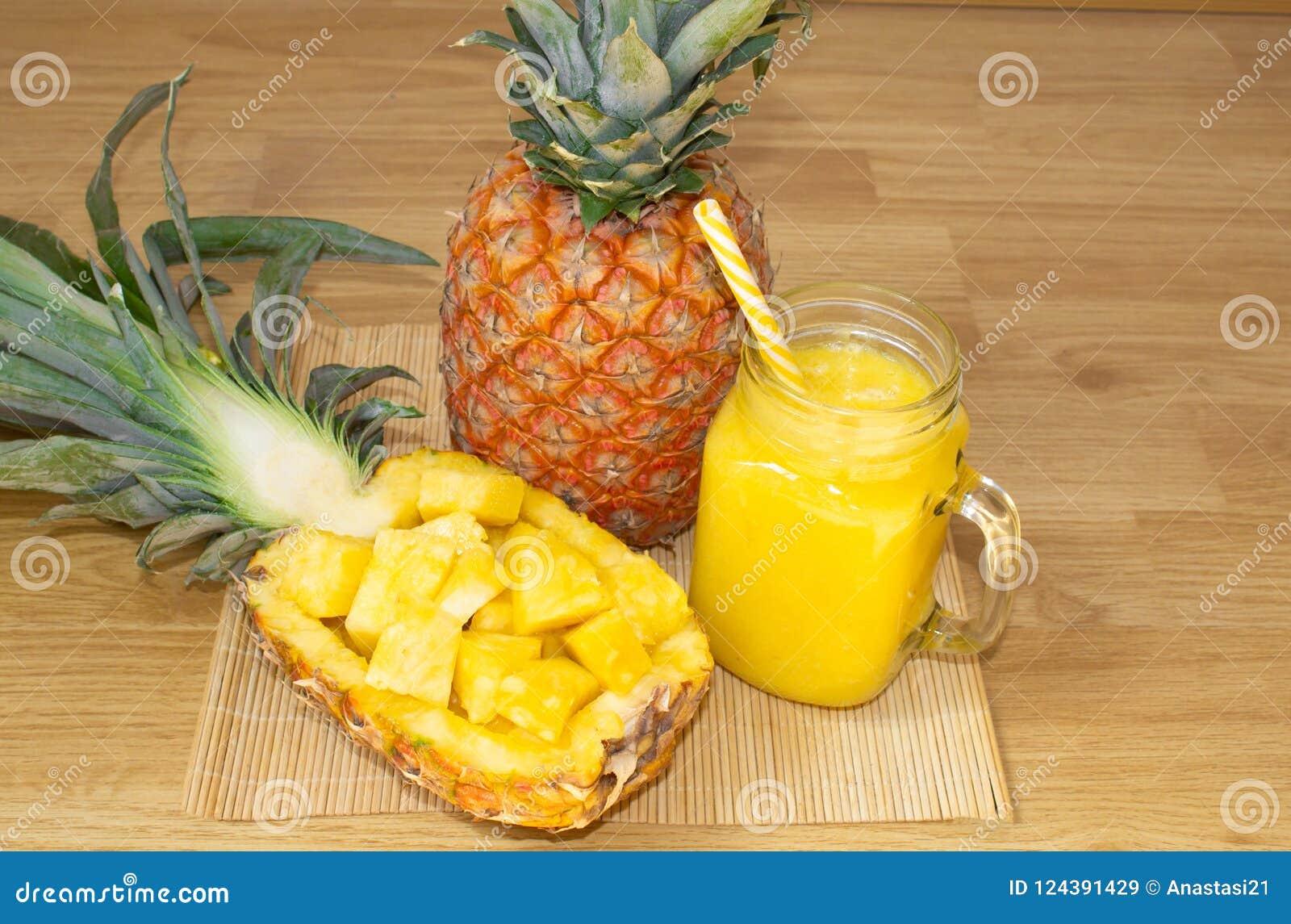 Ainda vida 1 Suco de abacaxi, batidos com o abacaxi fresco para o café da manhã na manhã em uma tabela de madeira detox