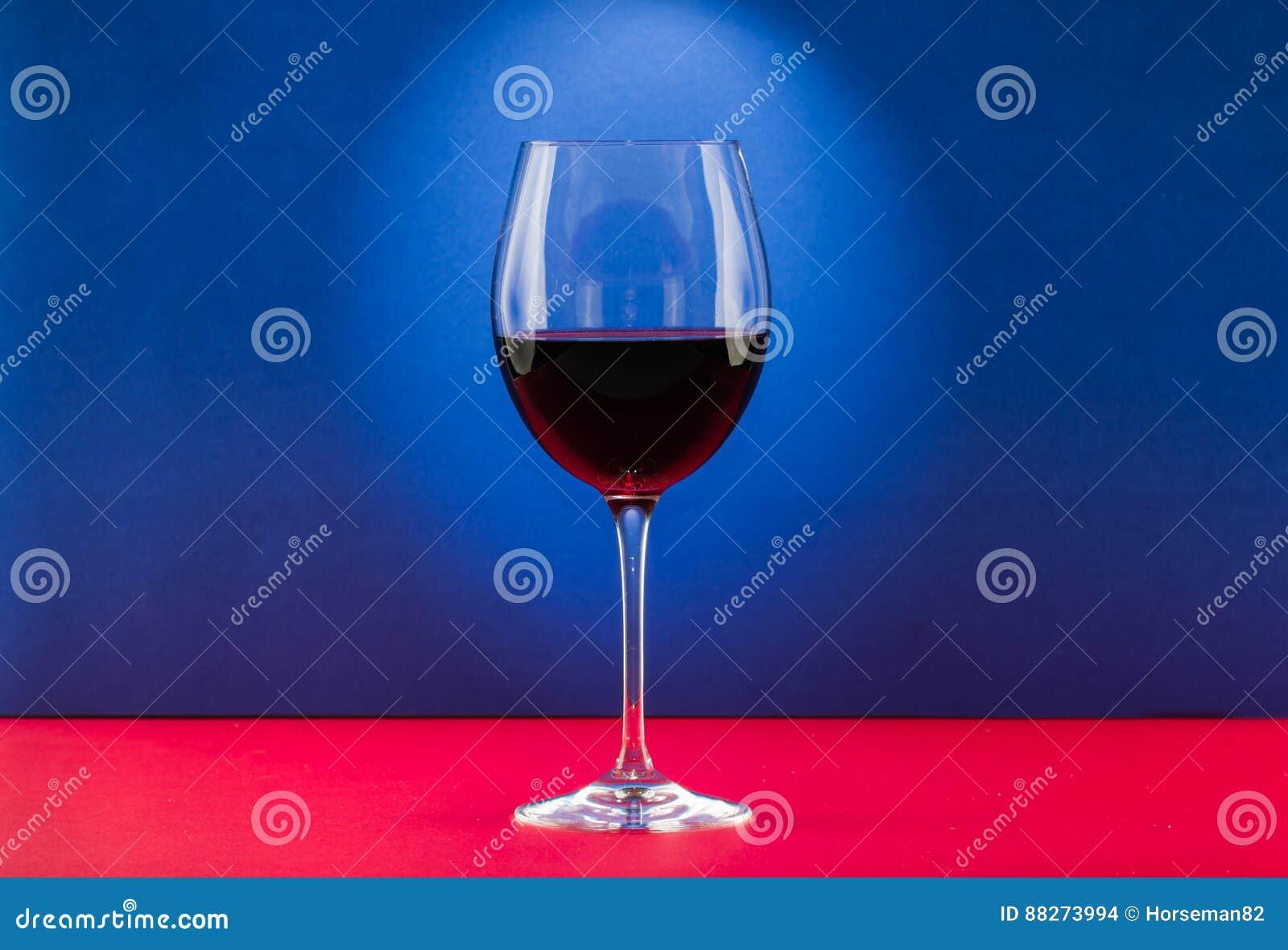 Ainda vidro da vida do vinho com efeito da luz agradável no fundo vermelho e azul