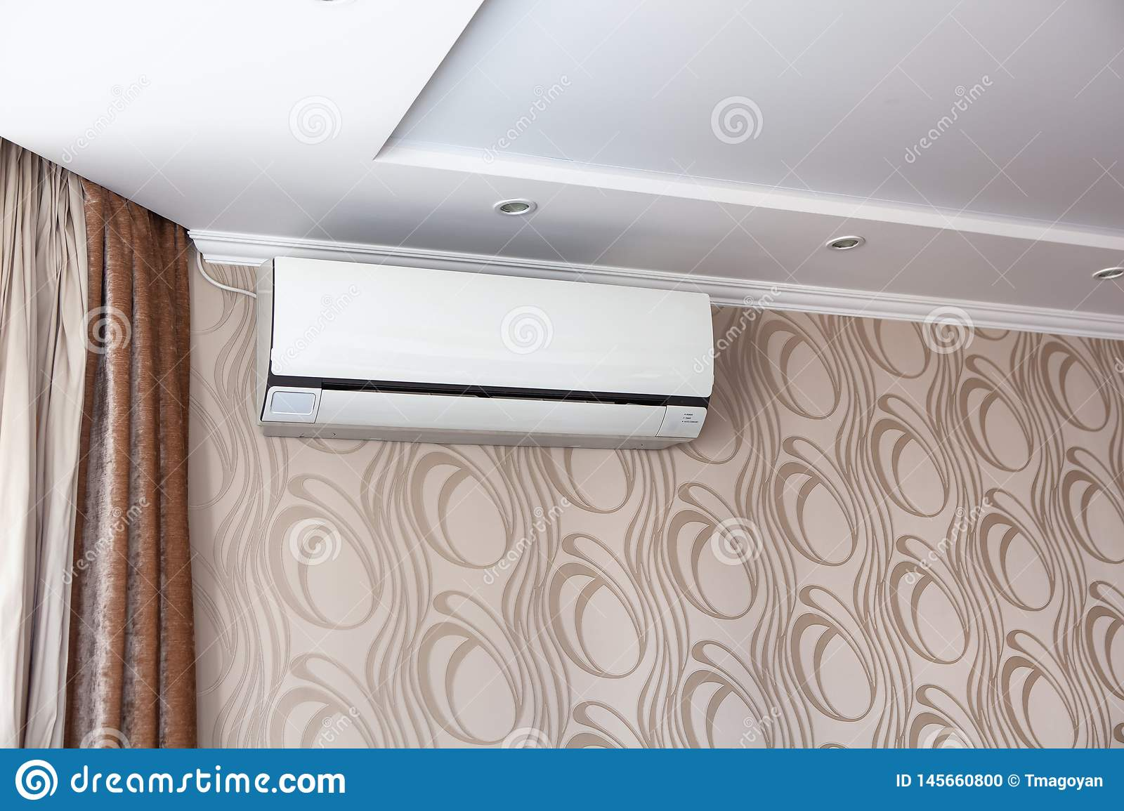 Air conditioning on the wall inside the room in apartment, switched off. Interior in calm beige tones