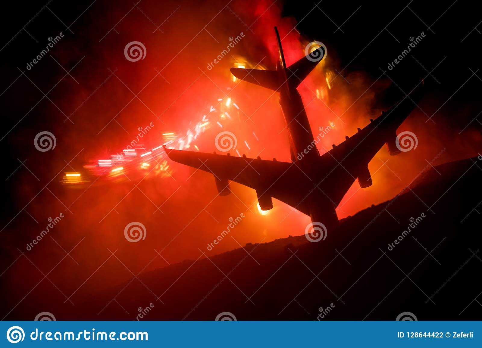 Air Crash. Burning falling plane. The plane crashed to the ground. Decorated with toy at dark fire background. Air accident concep