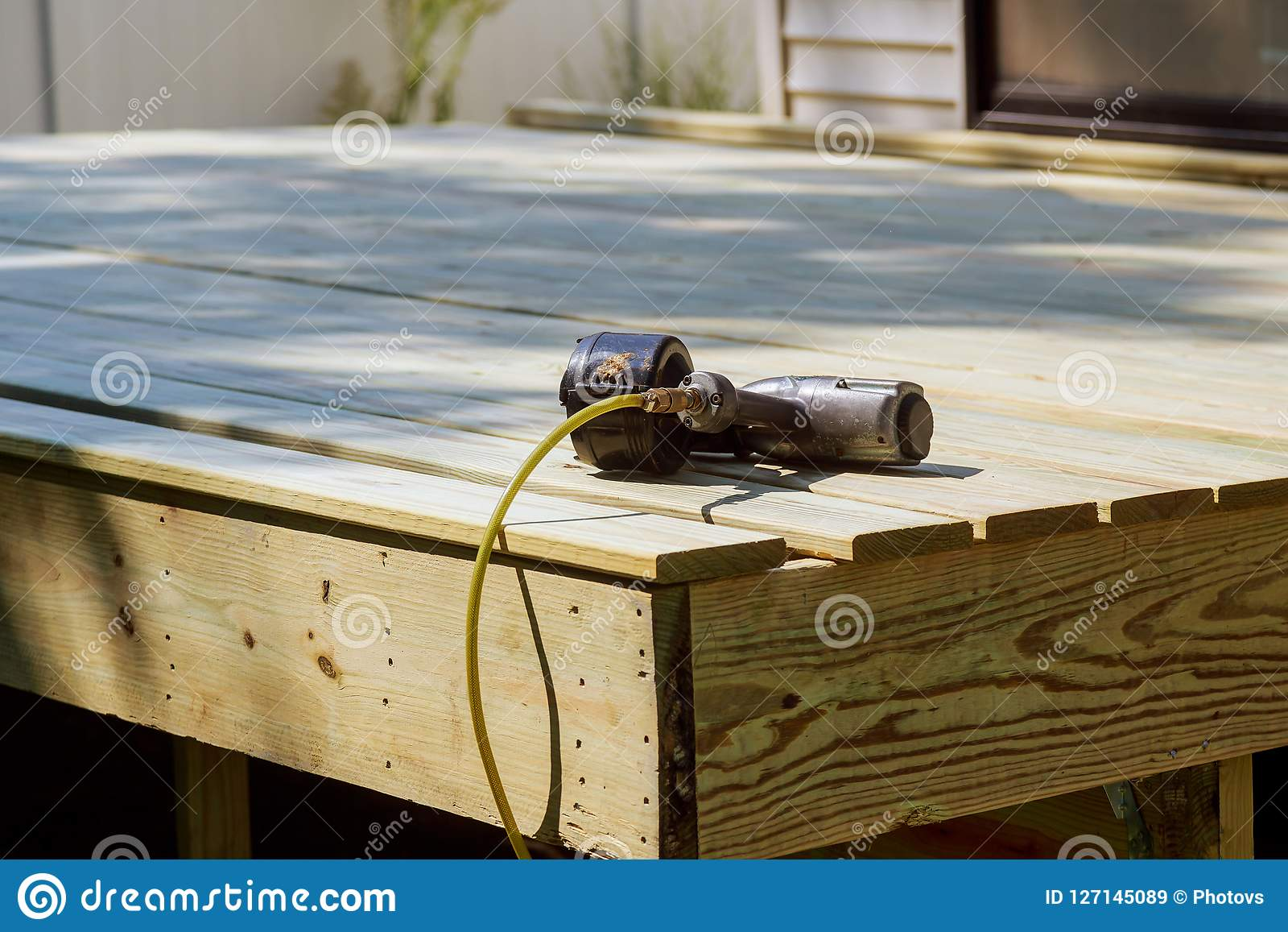 Worker Installing Wooden Floor Air Nail Gun On The Stock