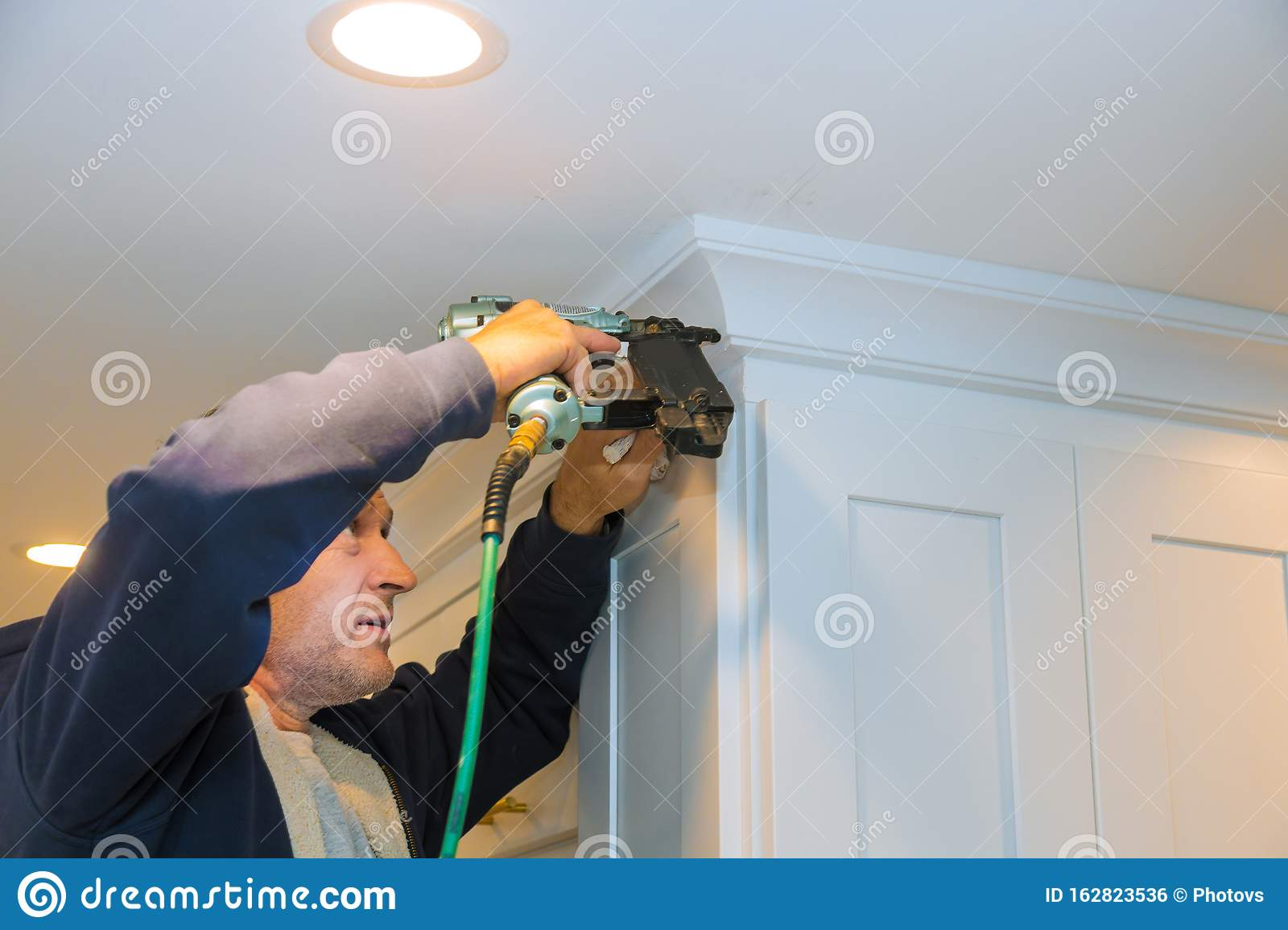 Air Nailer Tool Carpenter Using Nail Gun To Crown Moldings On Kitchen Cabinets With White Cabinets Stock Photo Image Of Interior Gaugefinishnailer 162823536