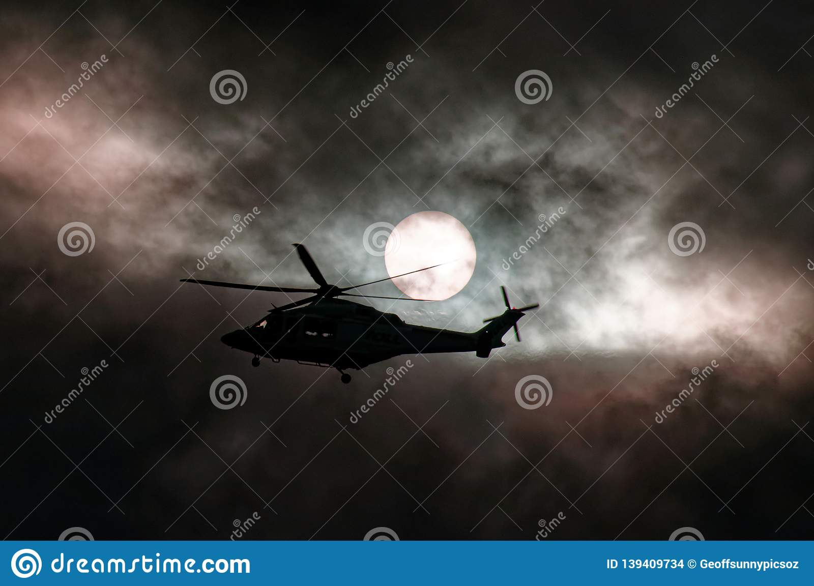 Airborne Helicopter in storm cloud sunset silhouette