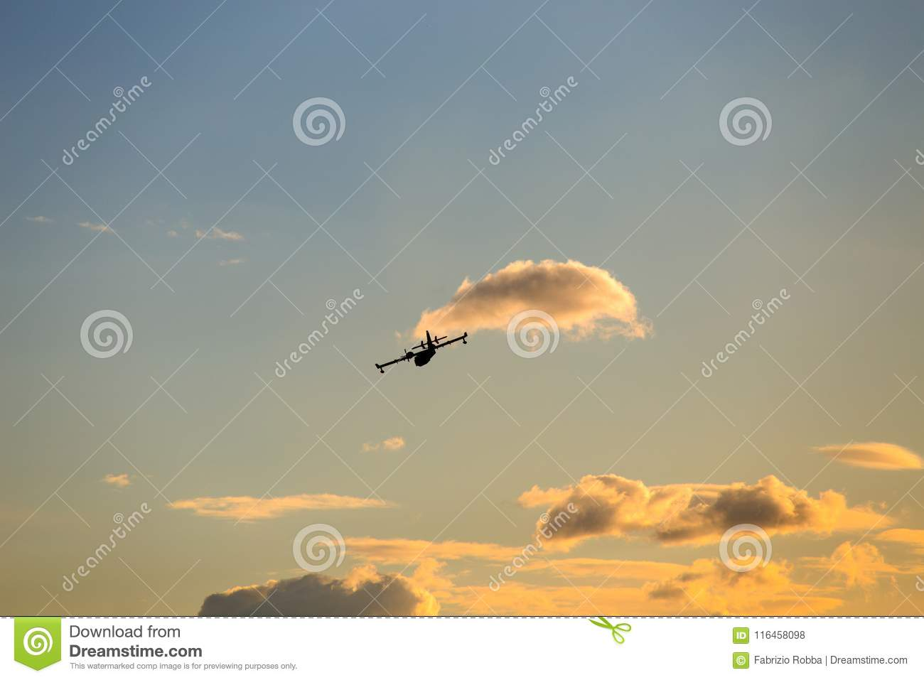 Aircraft silhouette flyes in the sky through the clouds at sunset