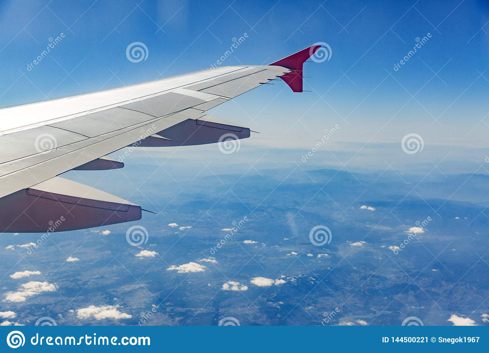 Aircraft wing on the clouds, flies on the city background