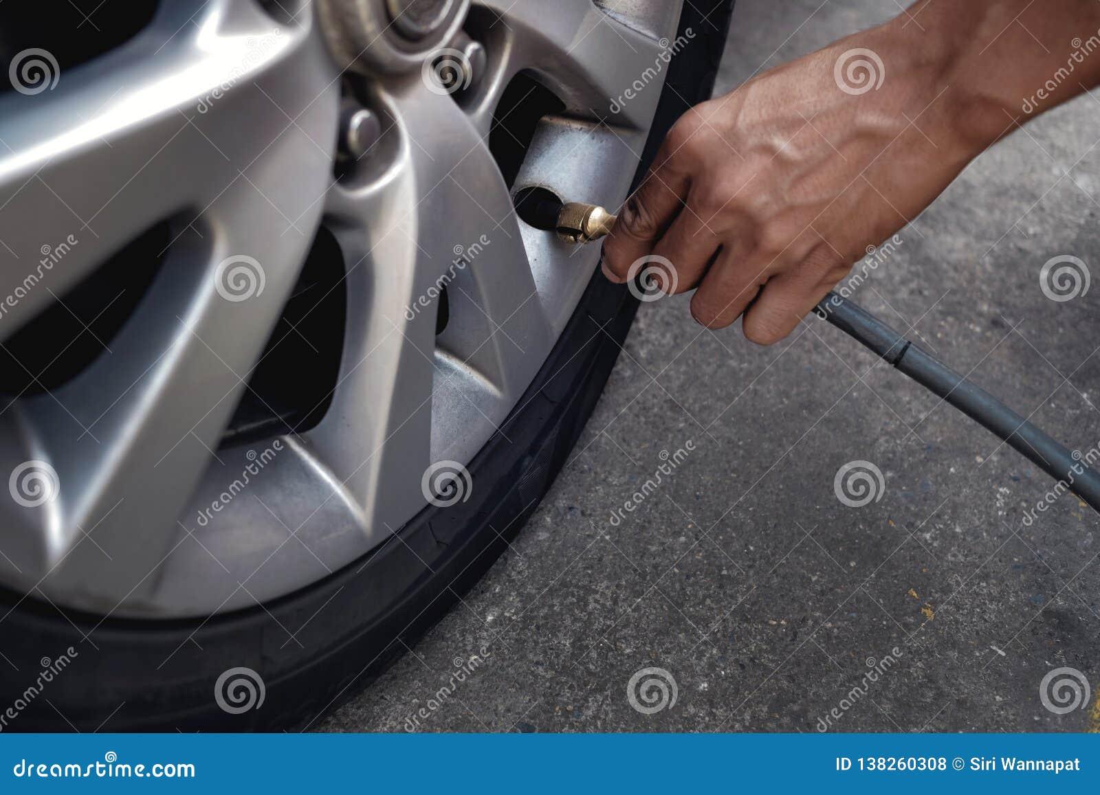 Aire de relleno del hombre en el neumático Conductor de coche Checking Air Pressure y mantenimiento su coche solo