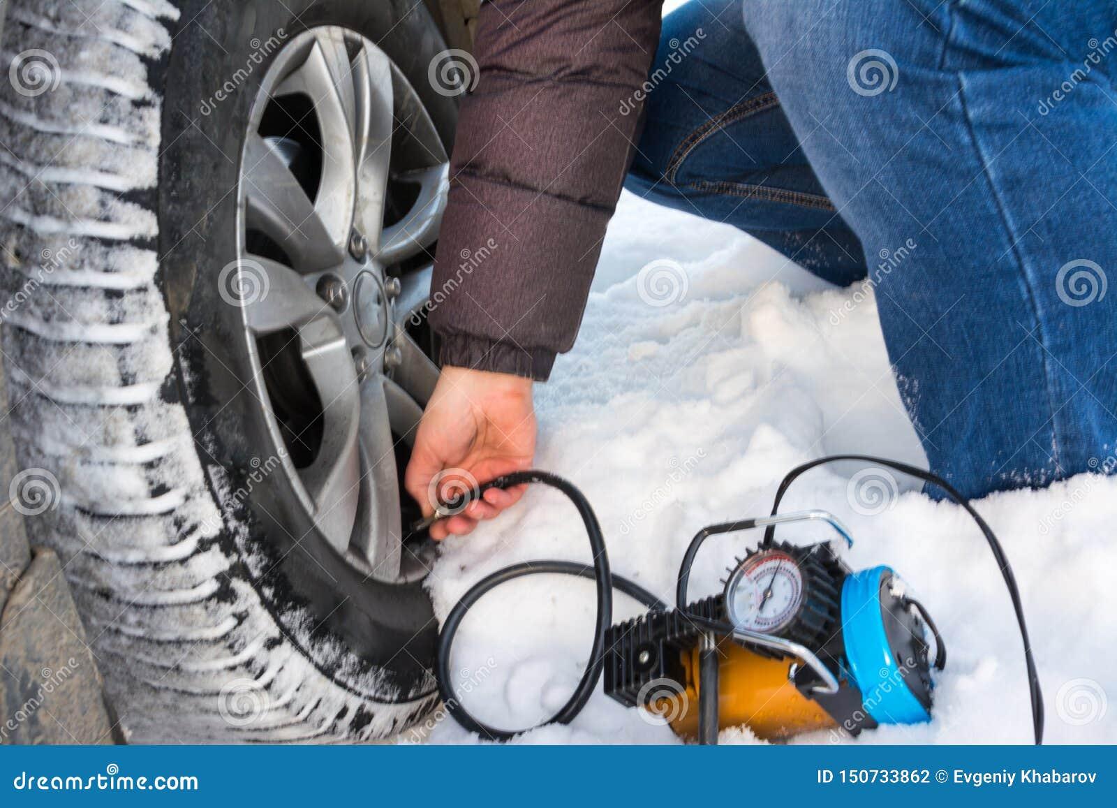 Aire de relleno en un neum?tico de coche Invierno Primer de reparar un compresor del uso del neumático desinflado