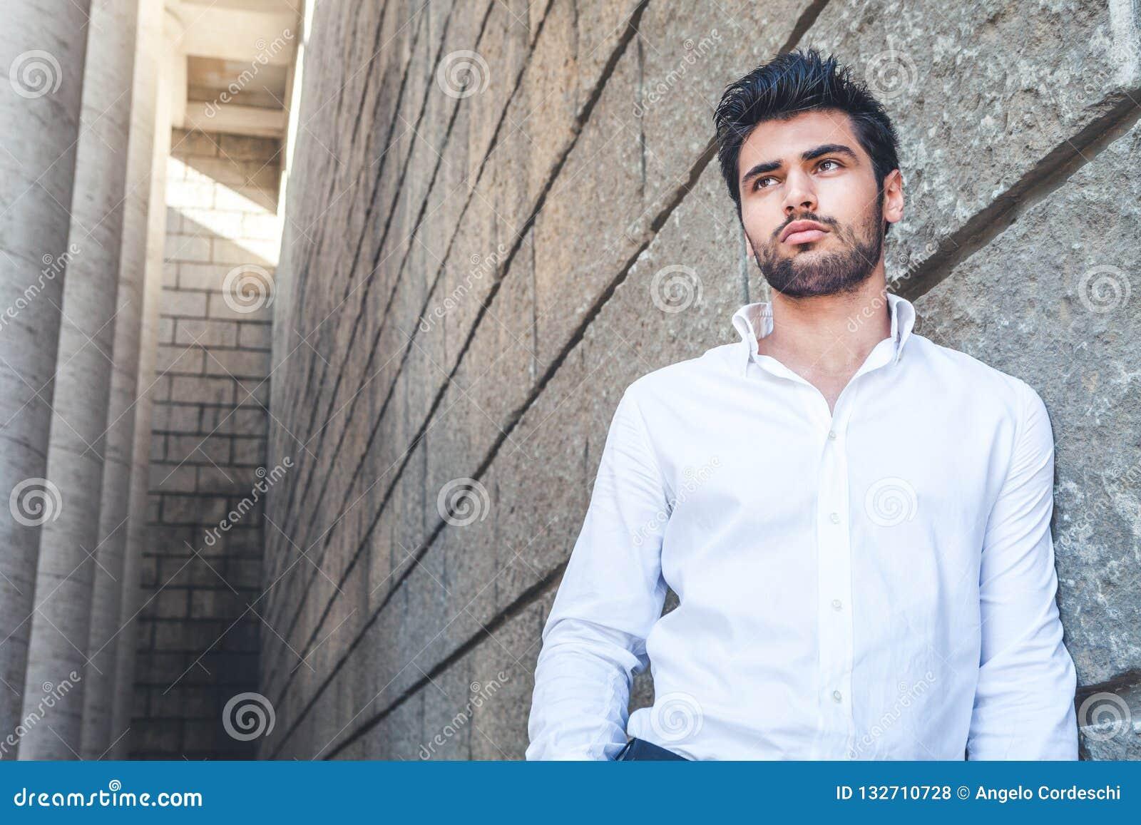 Aire libre del hombre joven con el espacio libre cerca Camisa blanca, pelo de moda y barba