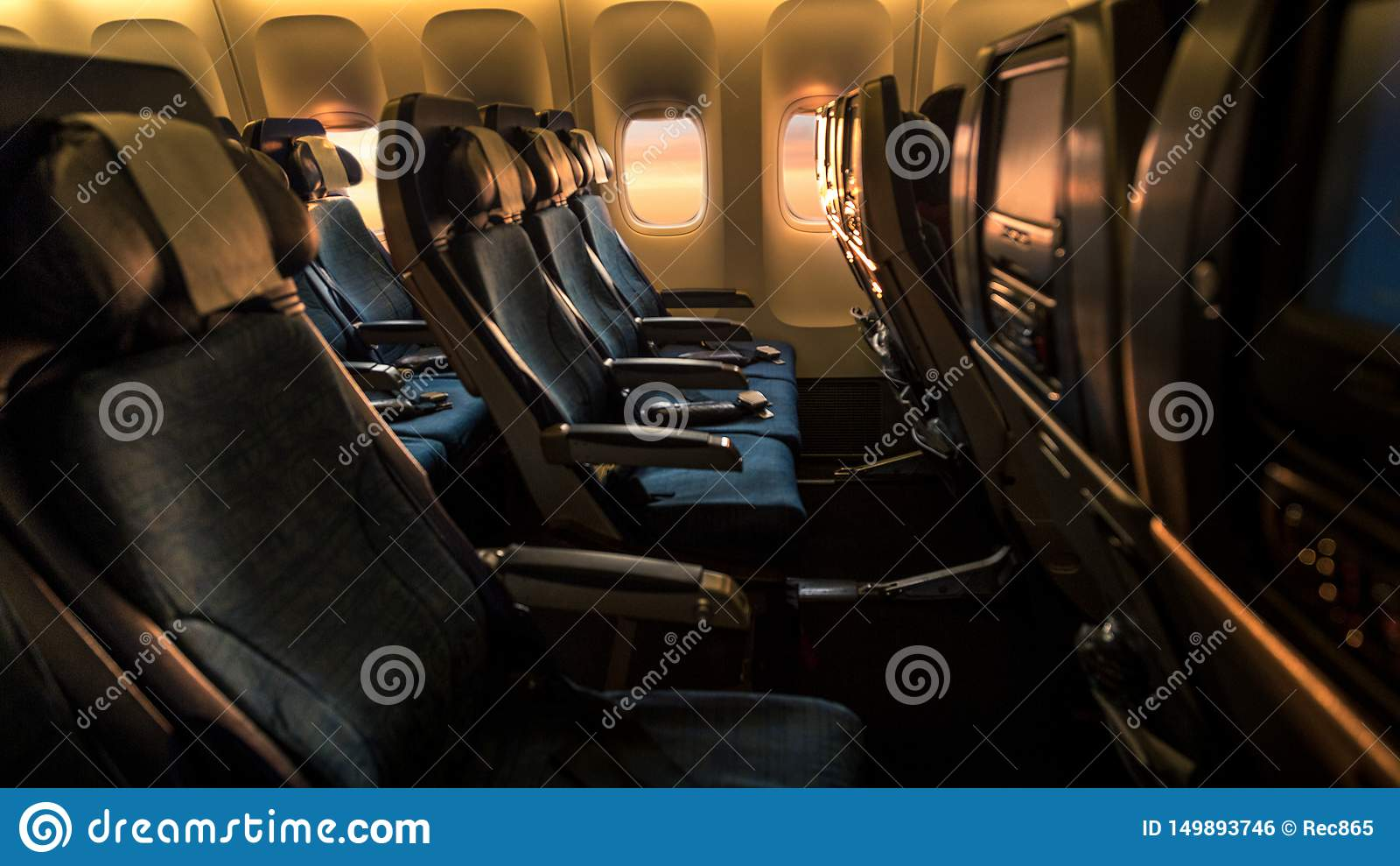 Airplane empty cabin with a beautiful sunset orange light