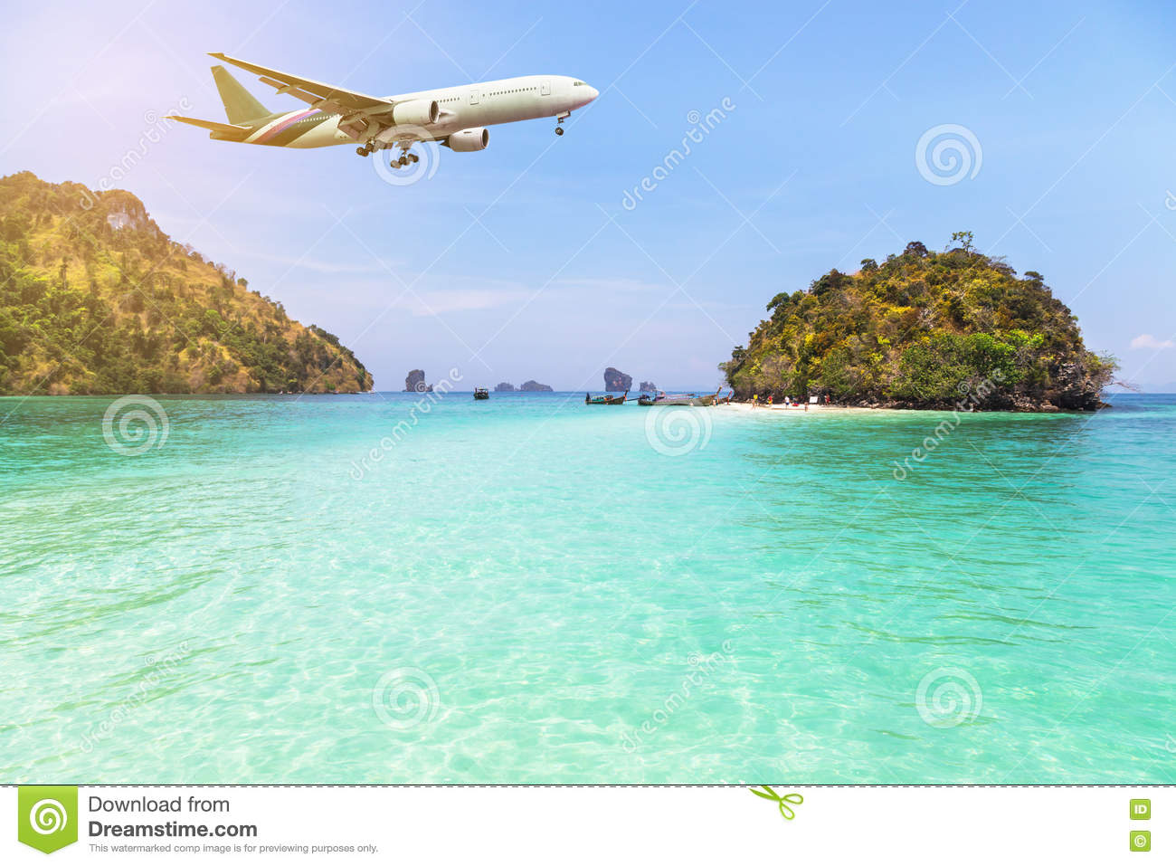 Airplane flying over above tropical island in the sea.