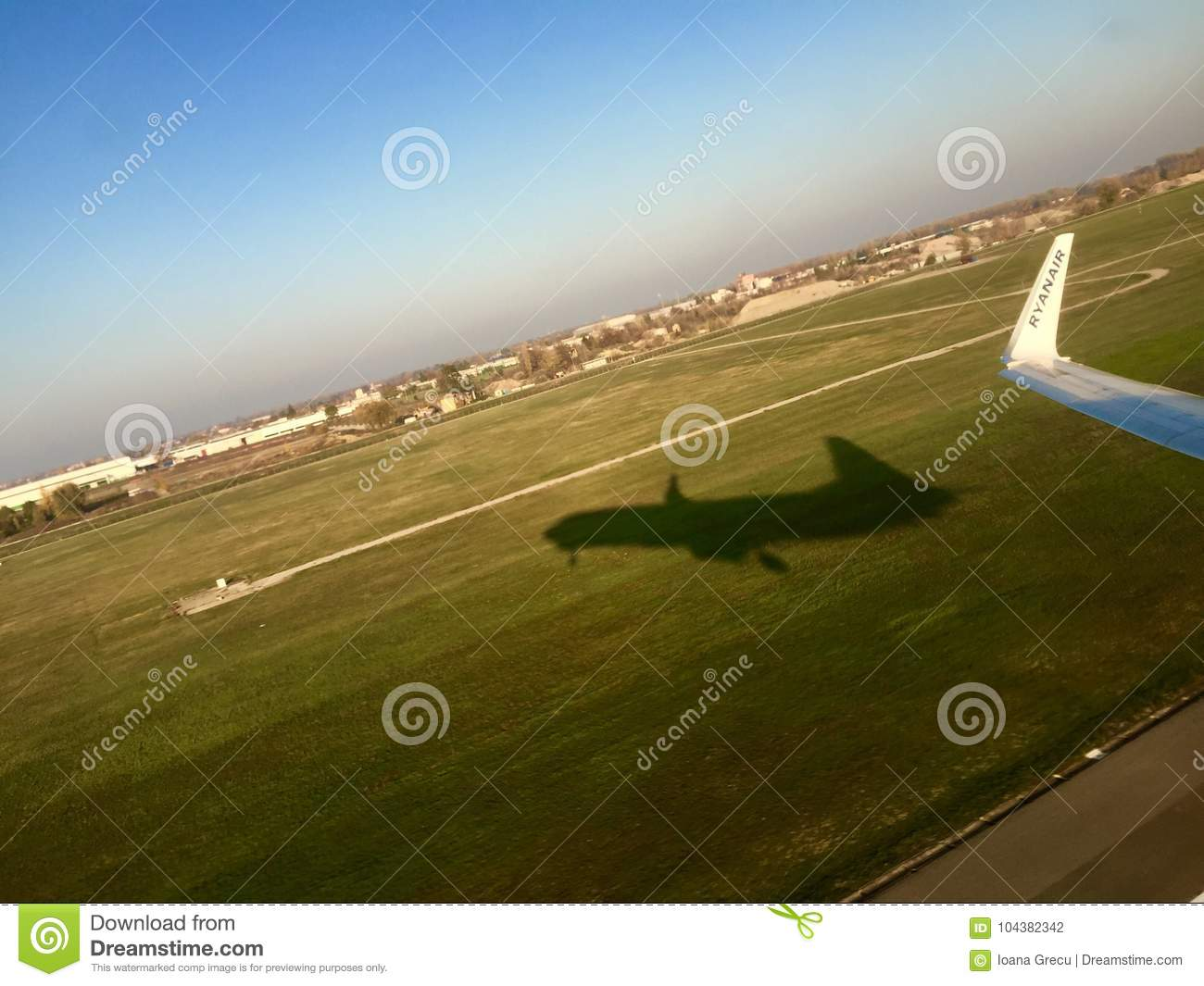 Airplane wing and shadow at take off