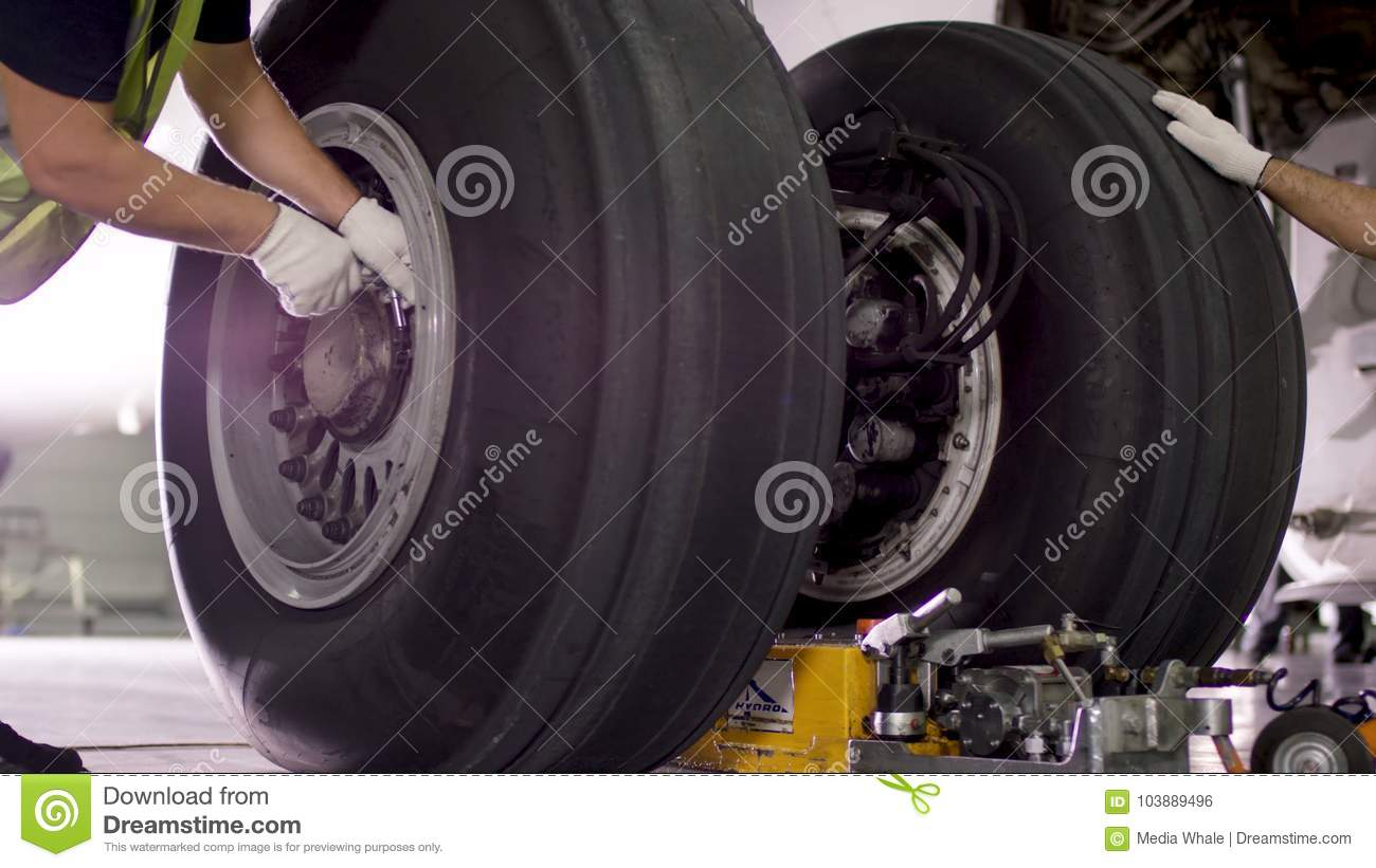 Airport worker checking chassis. Engine and chassis of the passenger airplane under heavy maintenance. Engineer checks