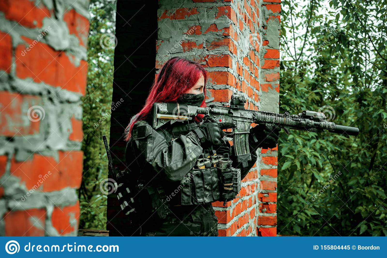 Airsoft red-hair woman in uniform with machine gun between brick walls. Soldier aims at the sight on the ruins. Horizontal photo