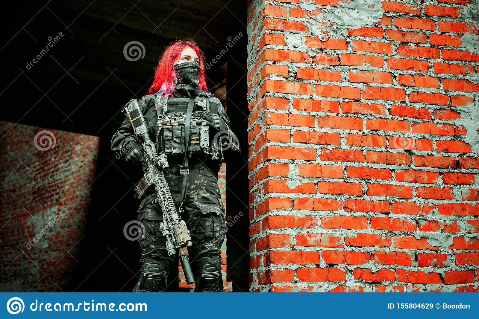 Airsoft red-hair woman in uniform with machine gun standing on ruins. Horizontal photo