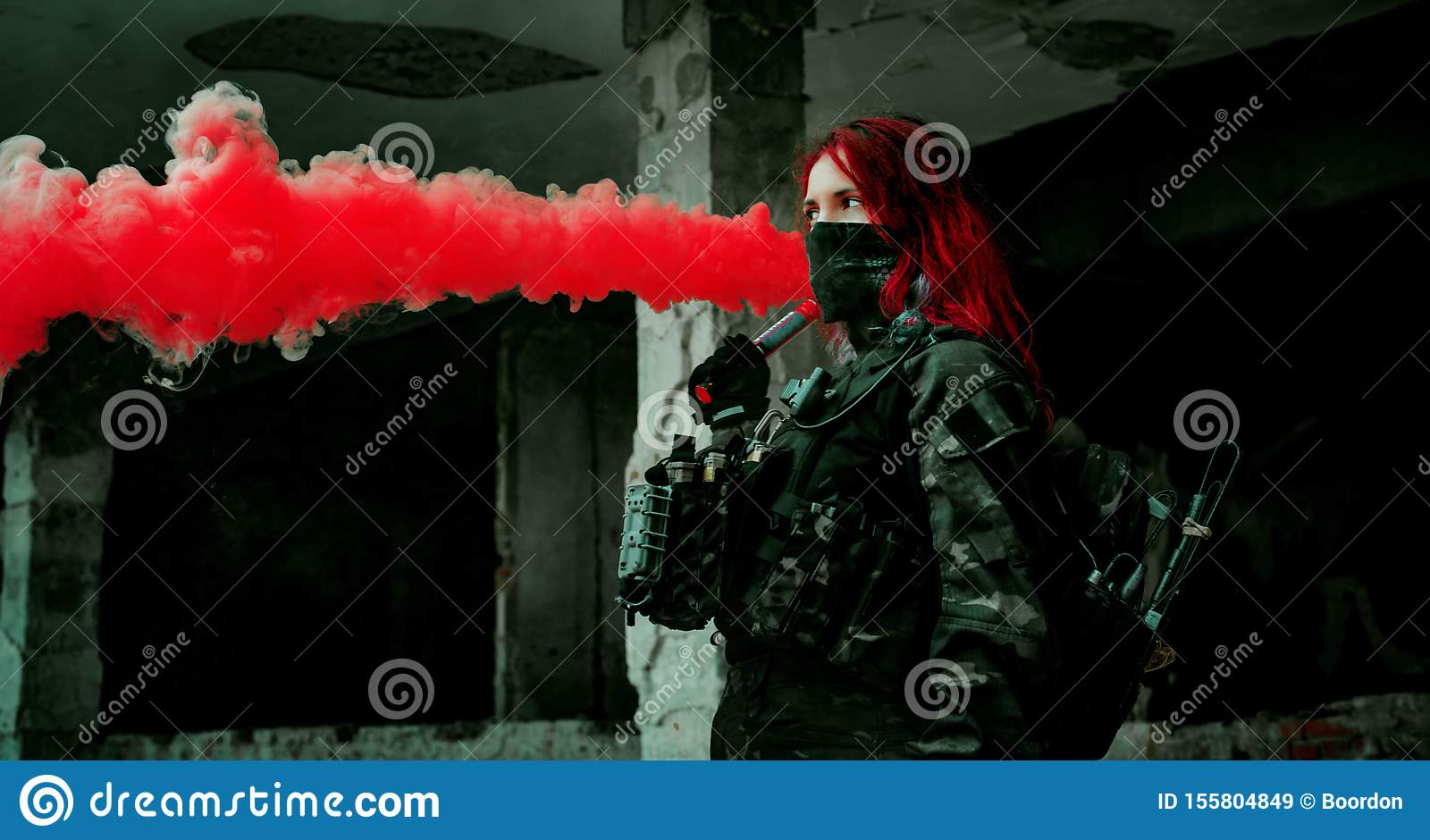 Airsoft red-hair woman in uniform with red smoke in hand. Close up soldier in broken building. Horizontal photo