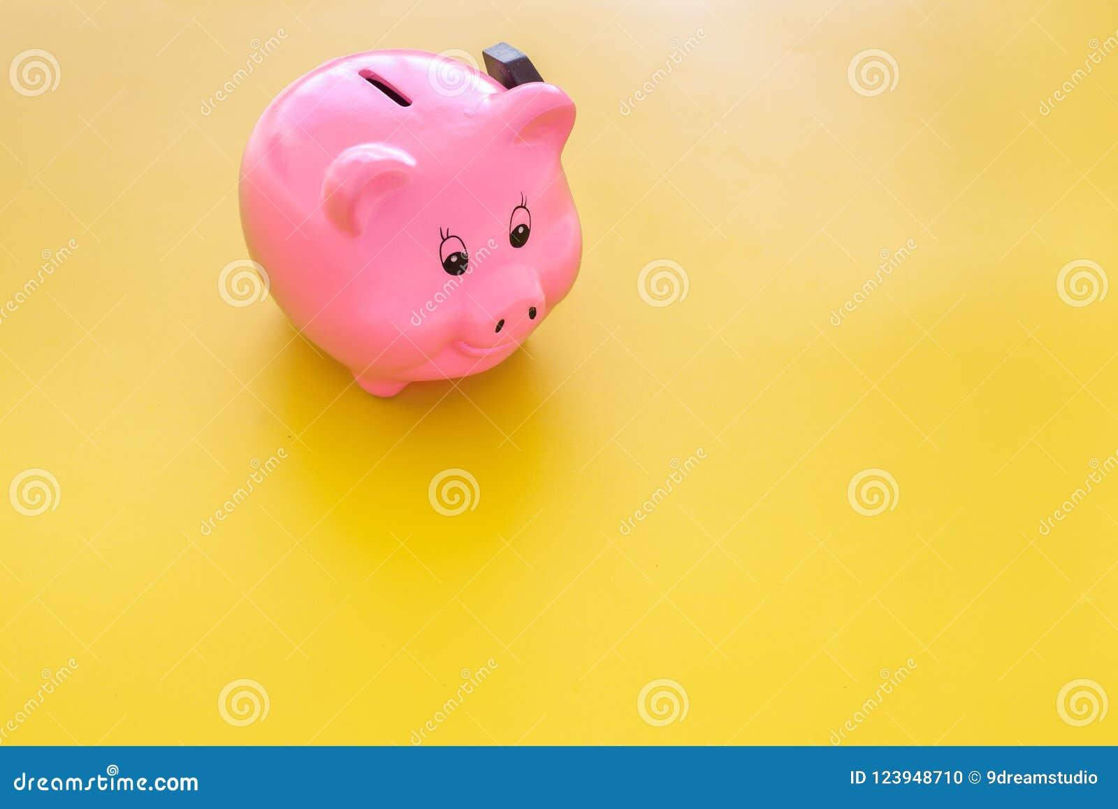 Aislado en blanco Moneybox en la forma del cerdo cerca del martillo en espacio amarillo de la copia del fondo