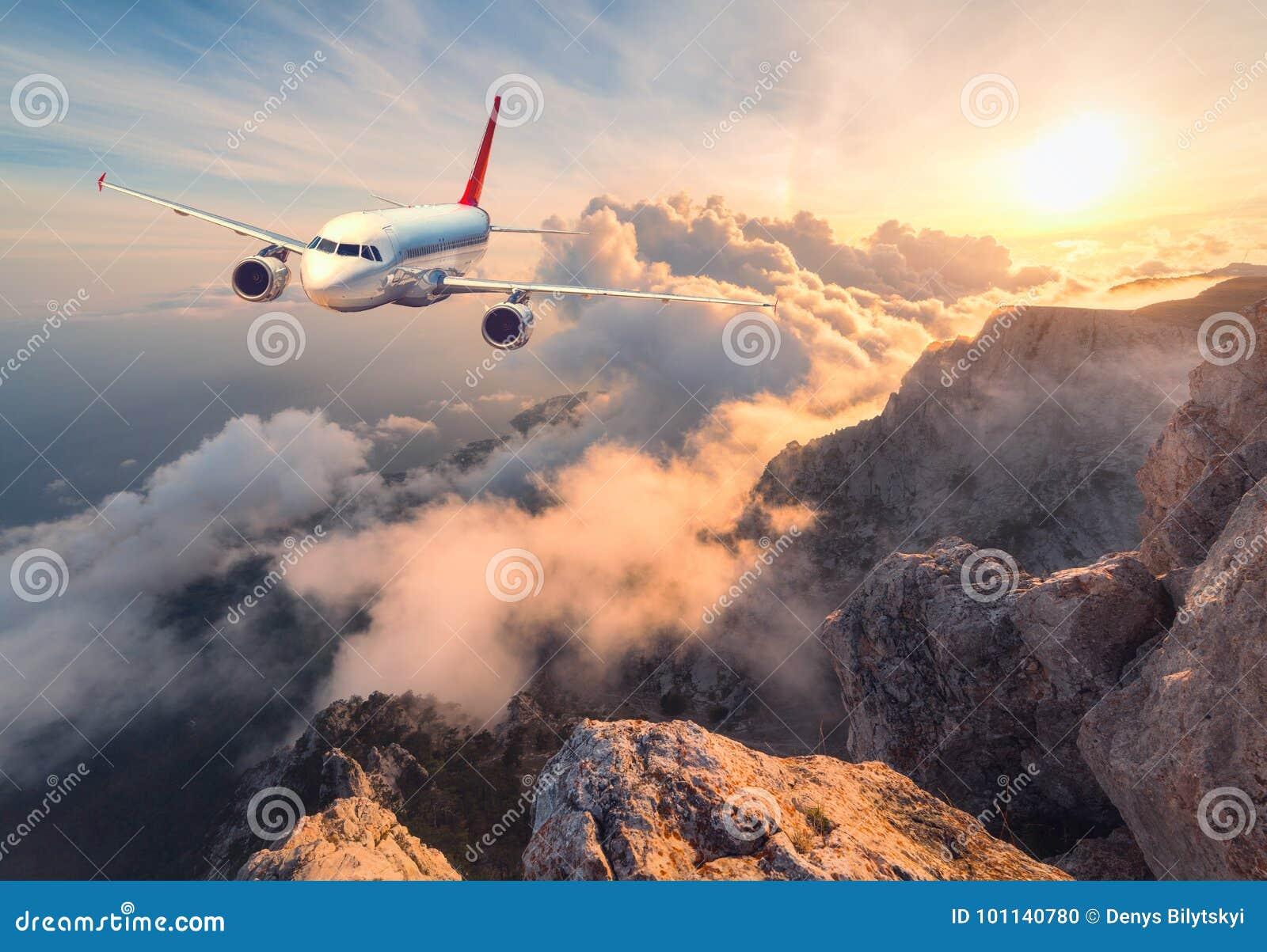 Ajardine con el aeroplano blanco del pasajero, las montañas, el mar y el cielo anaranjado