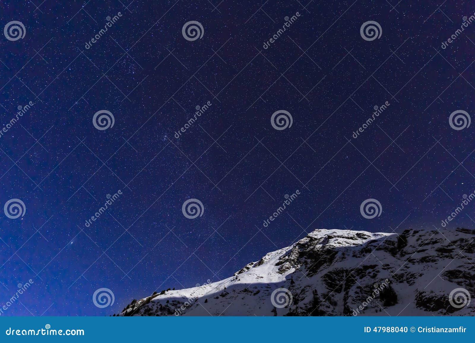 Ajardine con las montañas y el cielo azul en noche del invierno