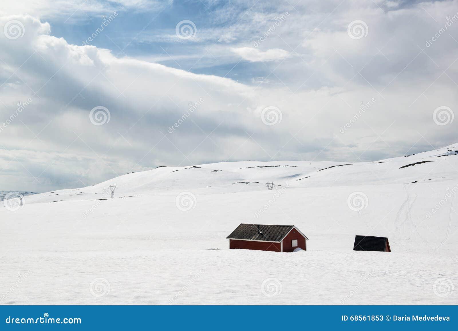 Ajardine en el día de verano soleado con nieve y casas solas, en el camino Aurlandsfjellet, Noruega