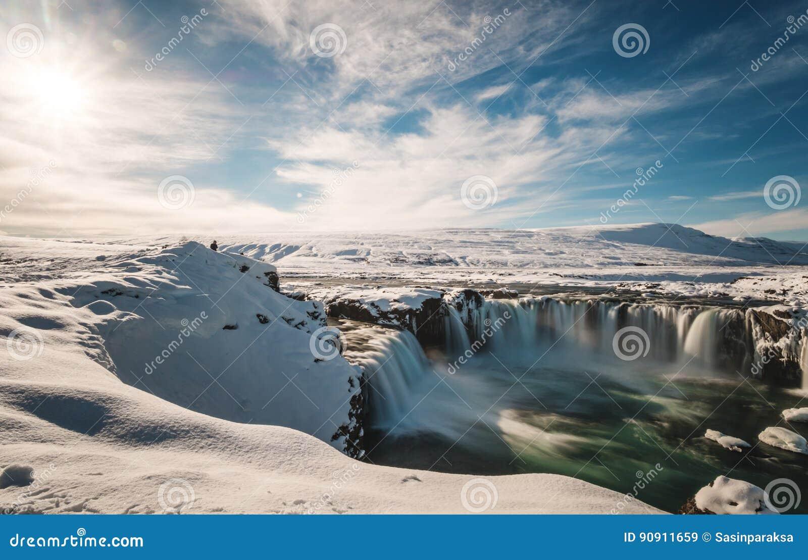 Ajardine, queda da água de Godafoss no inverno em Islândia com luz solar brilhante