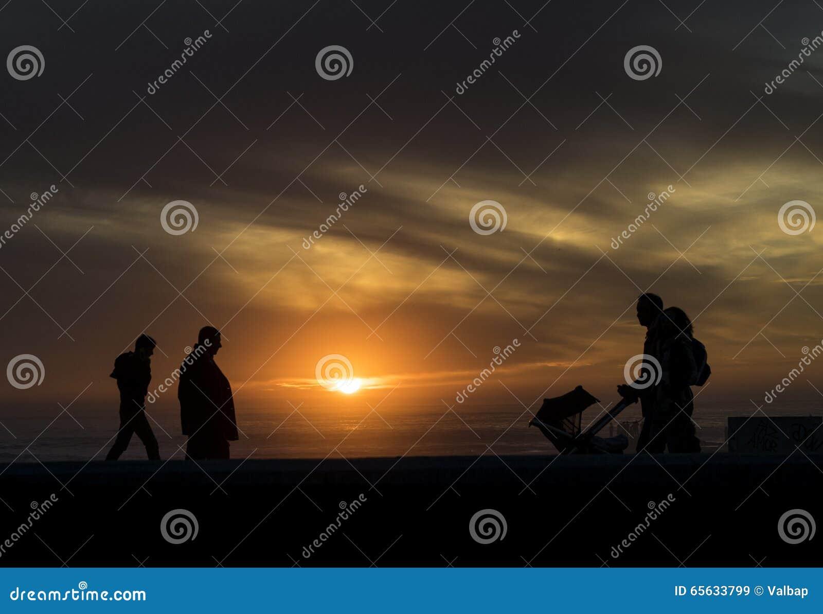Ajouter à un bébé marchant dans le coucher du soleil sur la plage