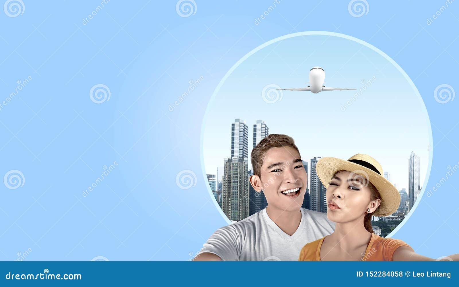 Ajouter asiatiques au chapeau prenant un selfie avec le fond de gratte-ciel