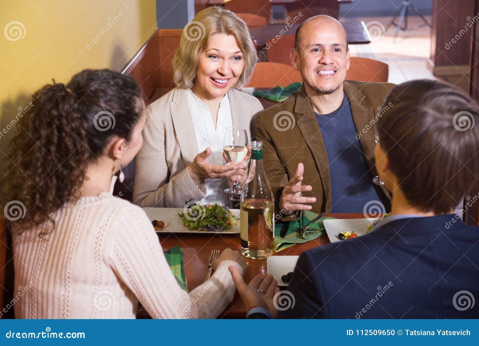 Ajouter mûrs aux amis ayant le dîner et le vin au restaurant