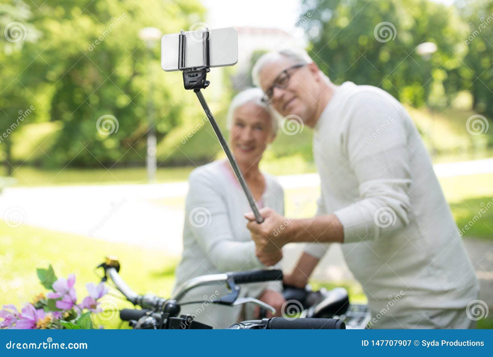 Ajouter sup?rieurs aux bicyclettes prenant le selfie au parc