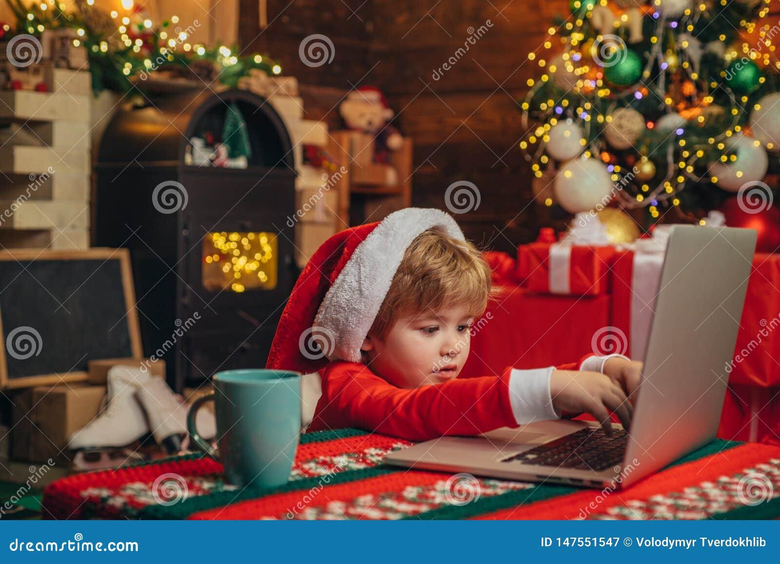 Ajudante pequeno de Santa E Criança do menino com o portátil perto da árvore de Natal compra