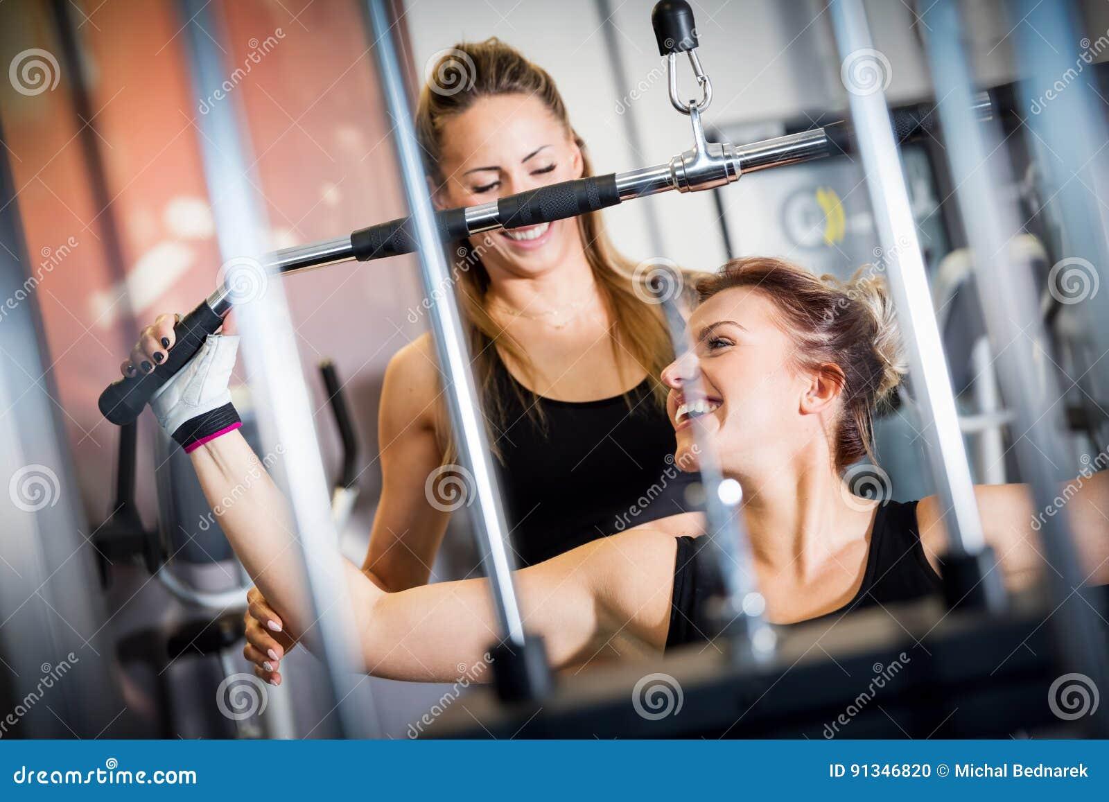 Ajudas pessoais do instrutor com exercício do equipamento do gym