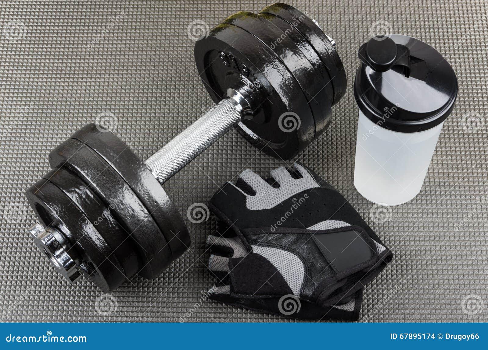 Ajustable哑铃、训练手套和振动器在席子