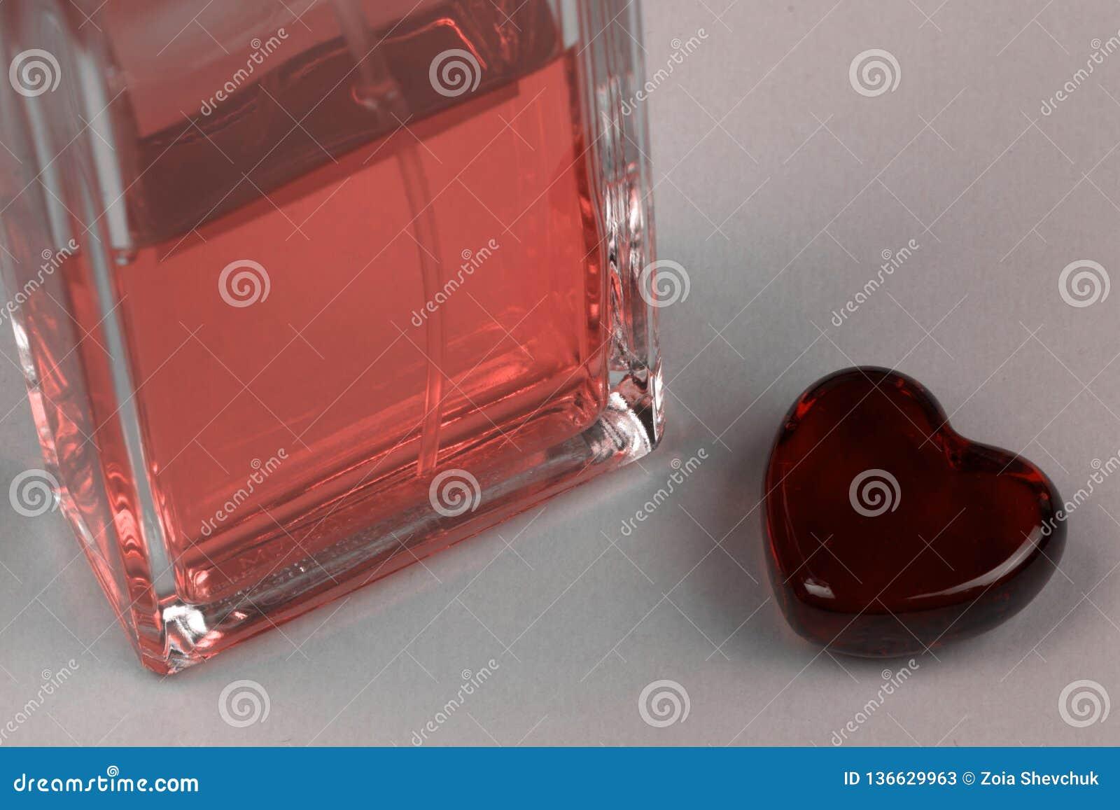 Ajuste da garrafa e do coração do parfume como um símbolo do presente com amor