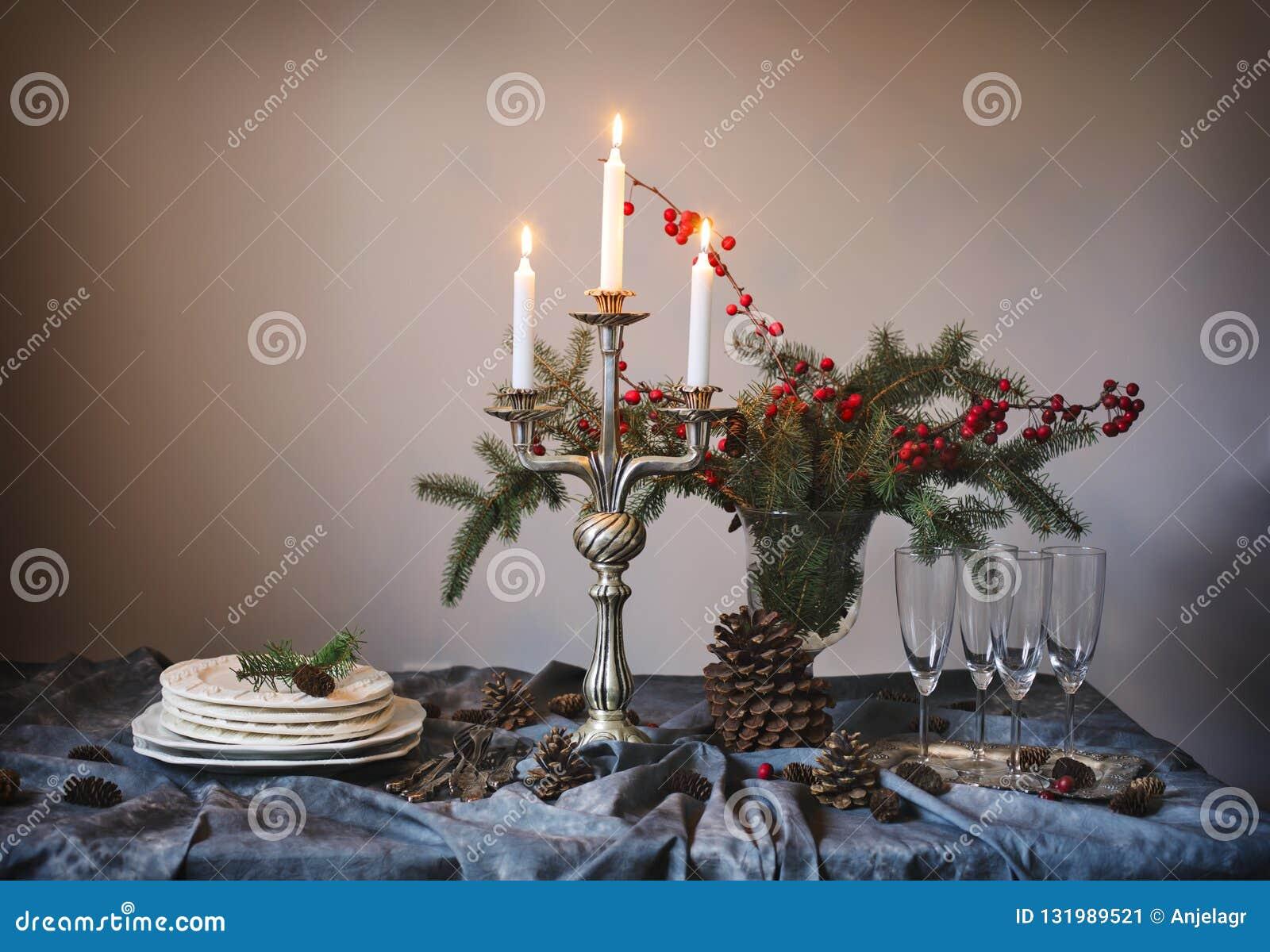 Ajuste da tabela do Natal Vidros e velas de Champagne na tabela