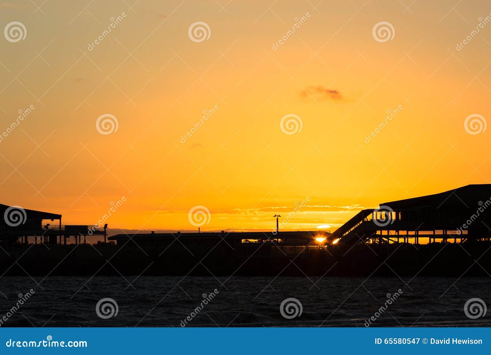 Ajuste de Sun atrás do cais da estação, Melbourne