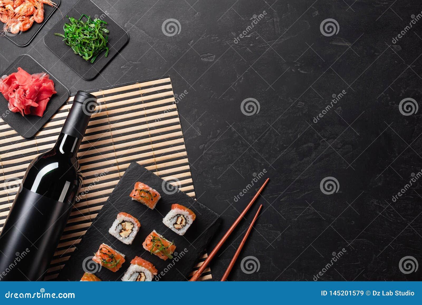 Ajuste do sushi e do maki com uma garrafa do vinho na tabela de pedra Vista superior