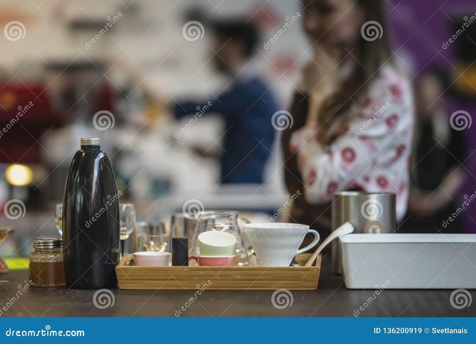 Ajuste dos pratos e dos acessórios para a preparação do café filtrado marcado na barra no fundo borrado com