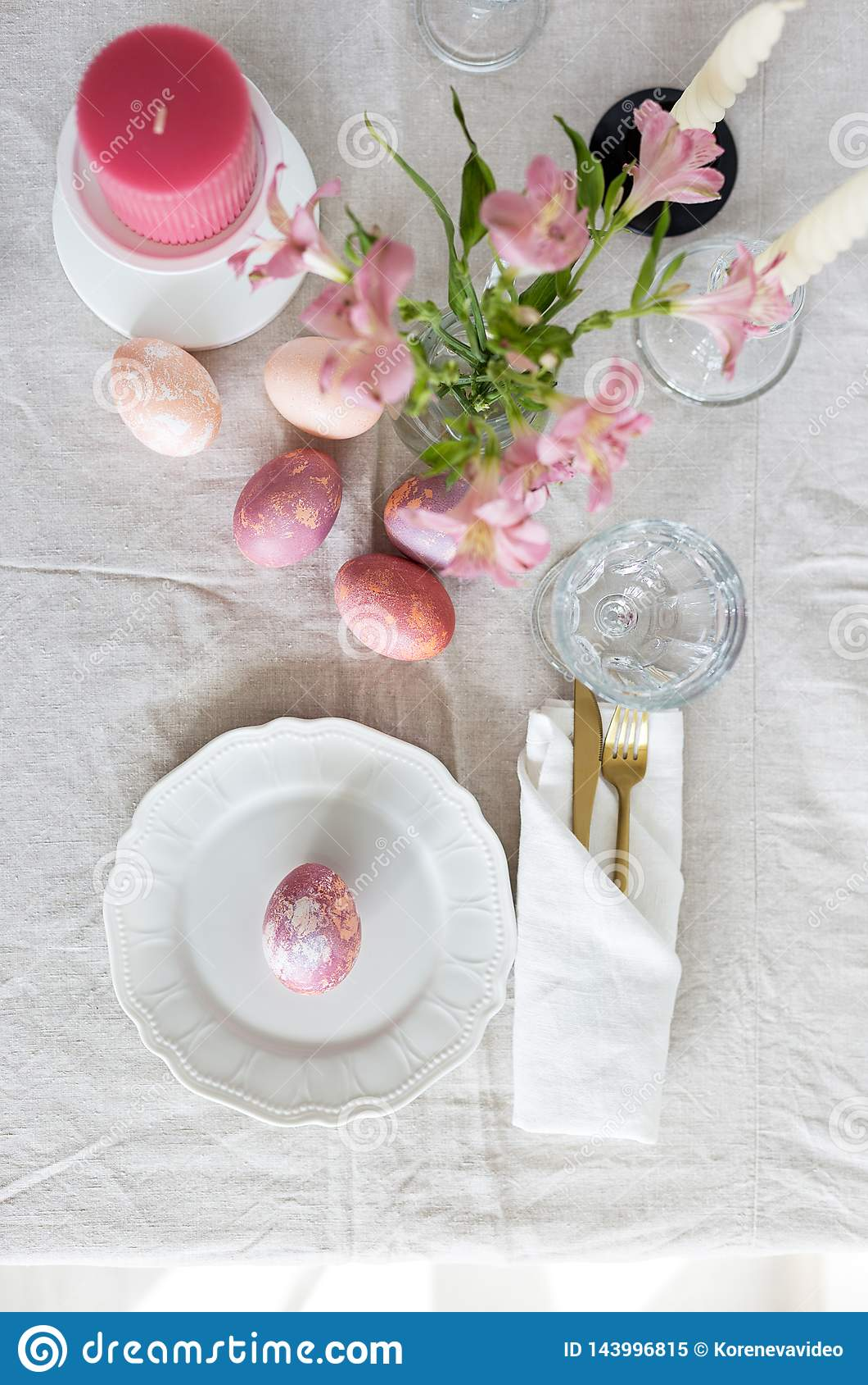 Ajuste festivo brillante de la tabla de Pascua con el mantel de lino, los huevos pintados y las flores