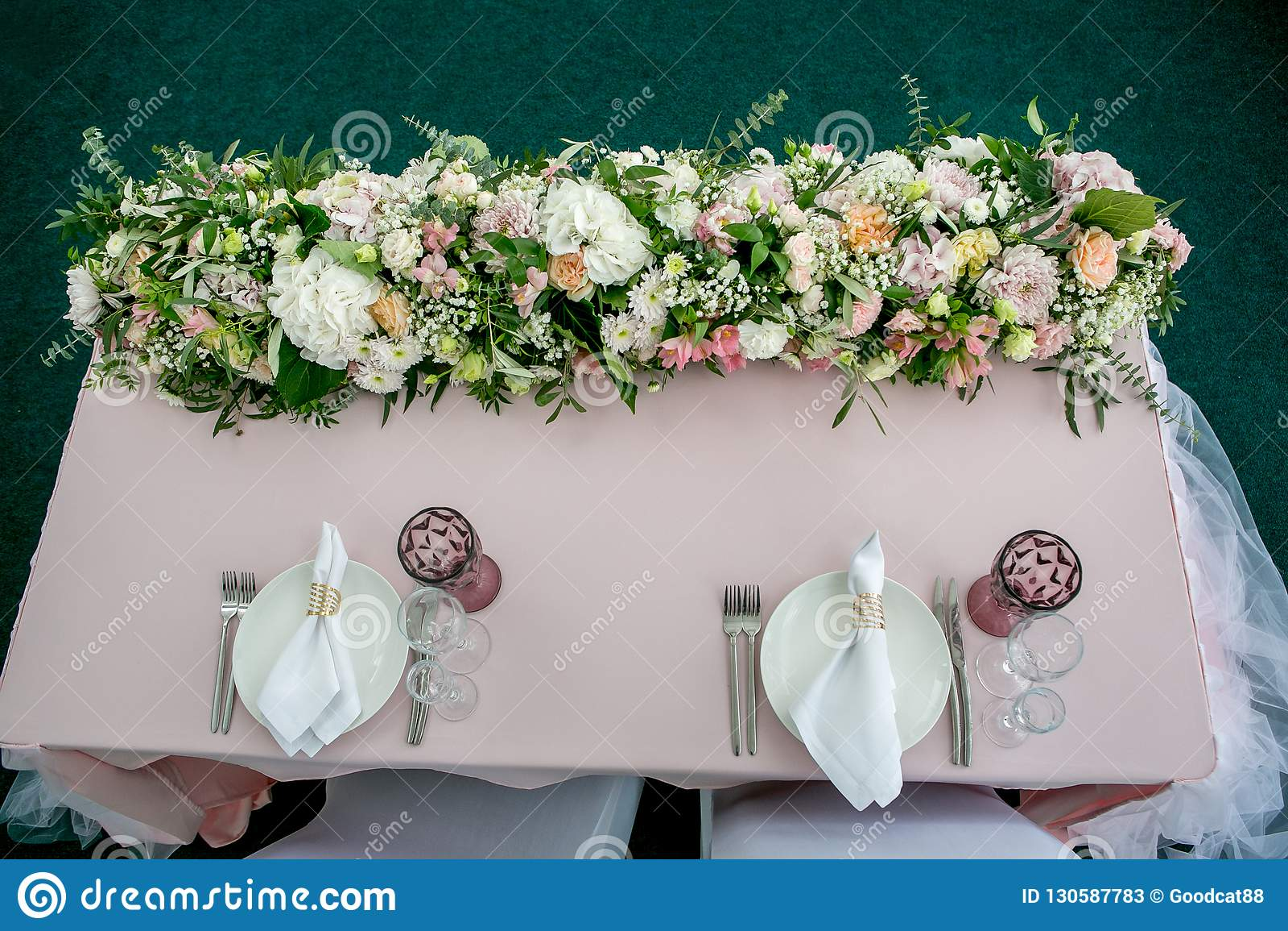 Ajuste hermoso de la tabla con loza y el forarrangement largo de las flores el partido, la recepción nupcial o el otro acontecimi