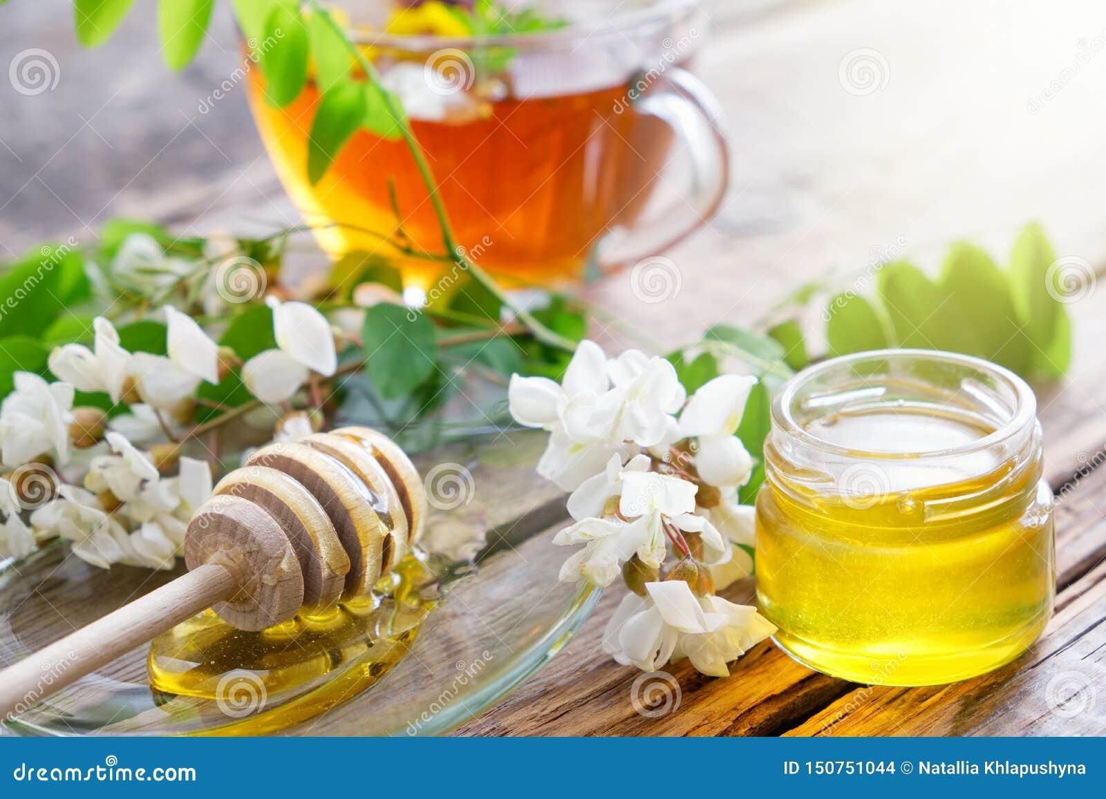 Akacjowi drzewni kwiaty miodowy słój, chochla i zdrowa ziołowa herbaciana filiżanka,